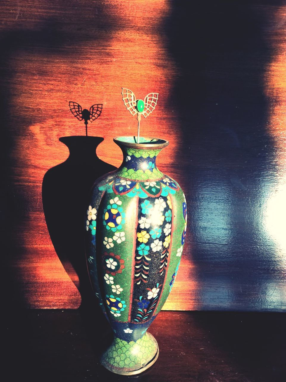 Colorful Patterned Urn Against Wooden Wall