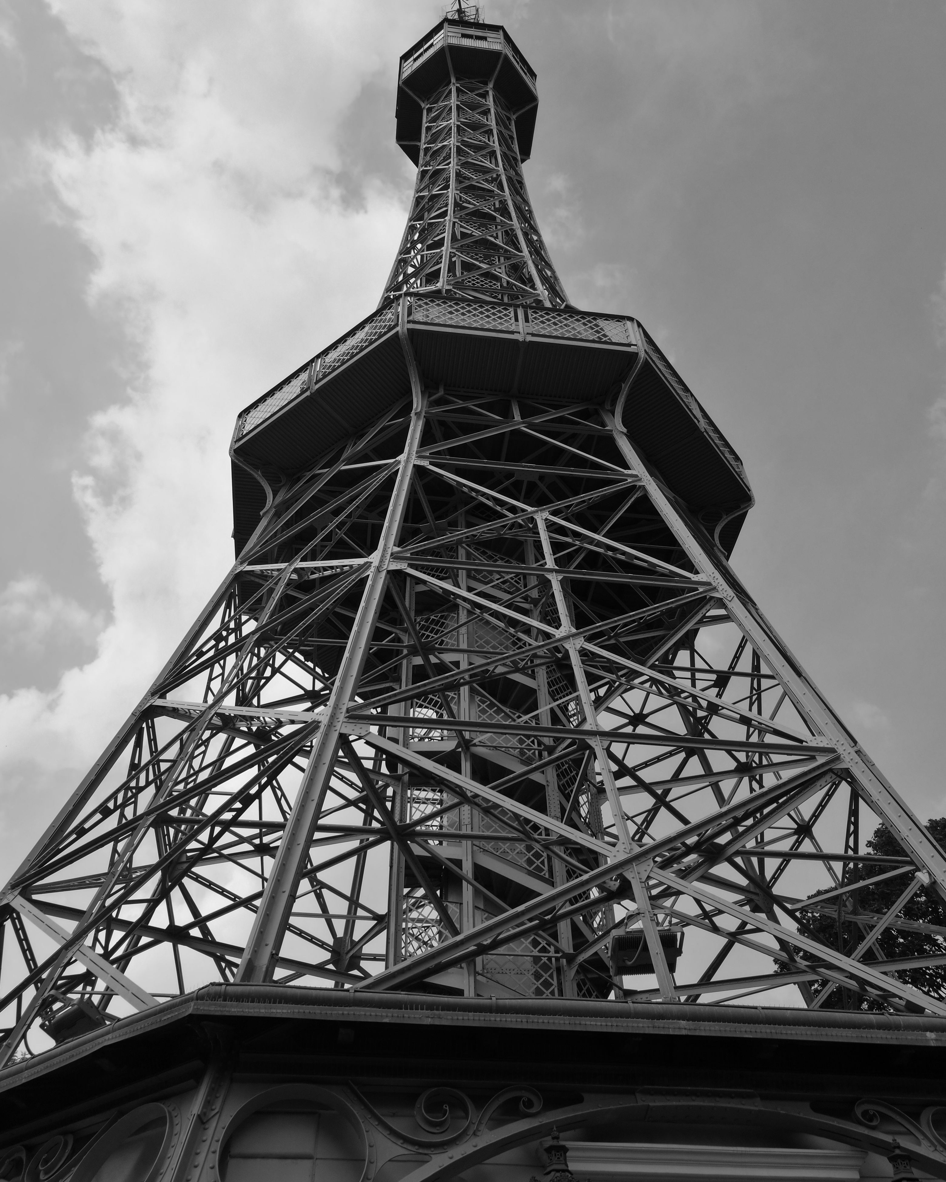low angle view, built structure, tower, architecture, eiffel tower, international landmark, famous place, tall - high, sky, metal, travel destinations, tourism, tall, iron - metal, capital cities, culture, cloud, cloud - sky, history, architectural feature, day, outdoors, monument, no people