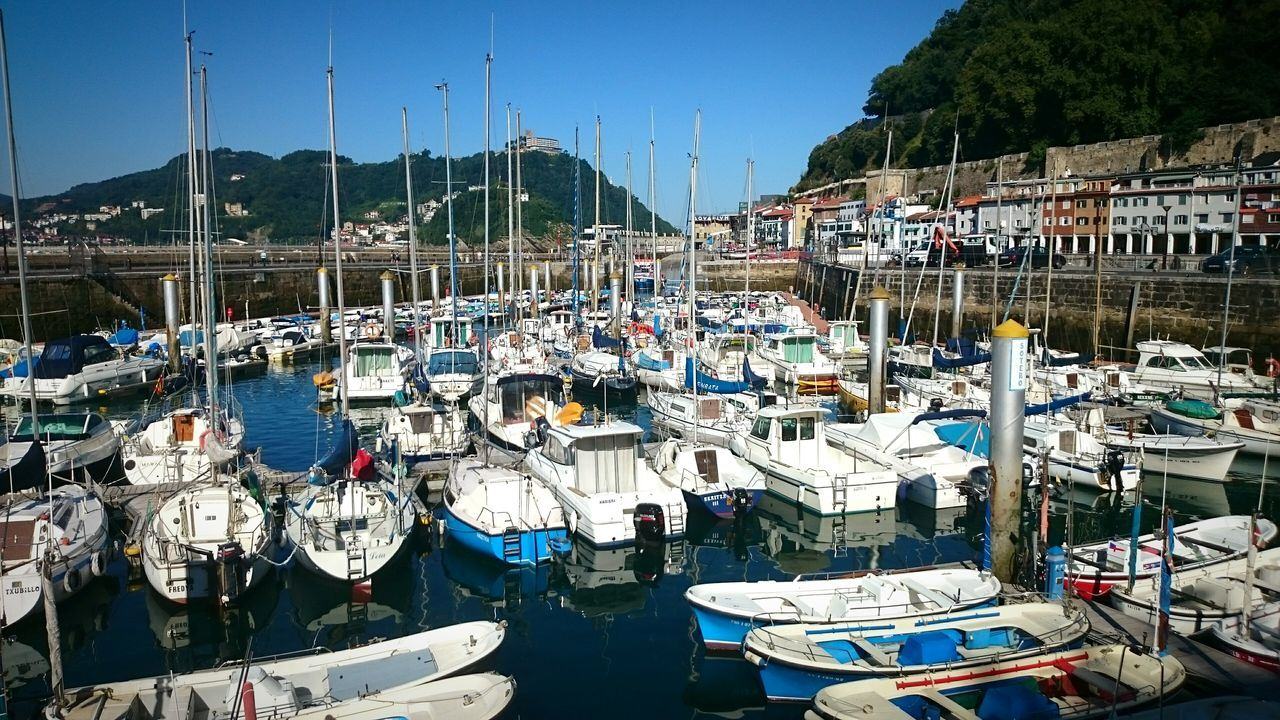 Boats Moored At Harbor By Town