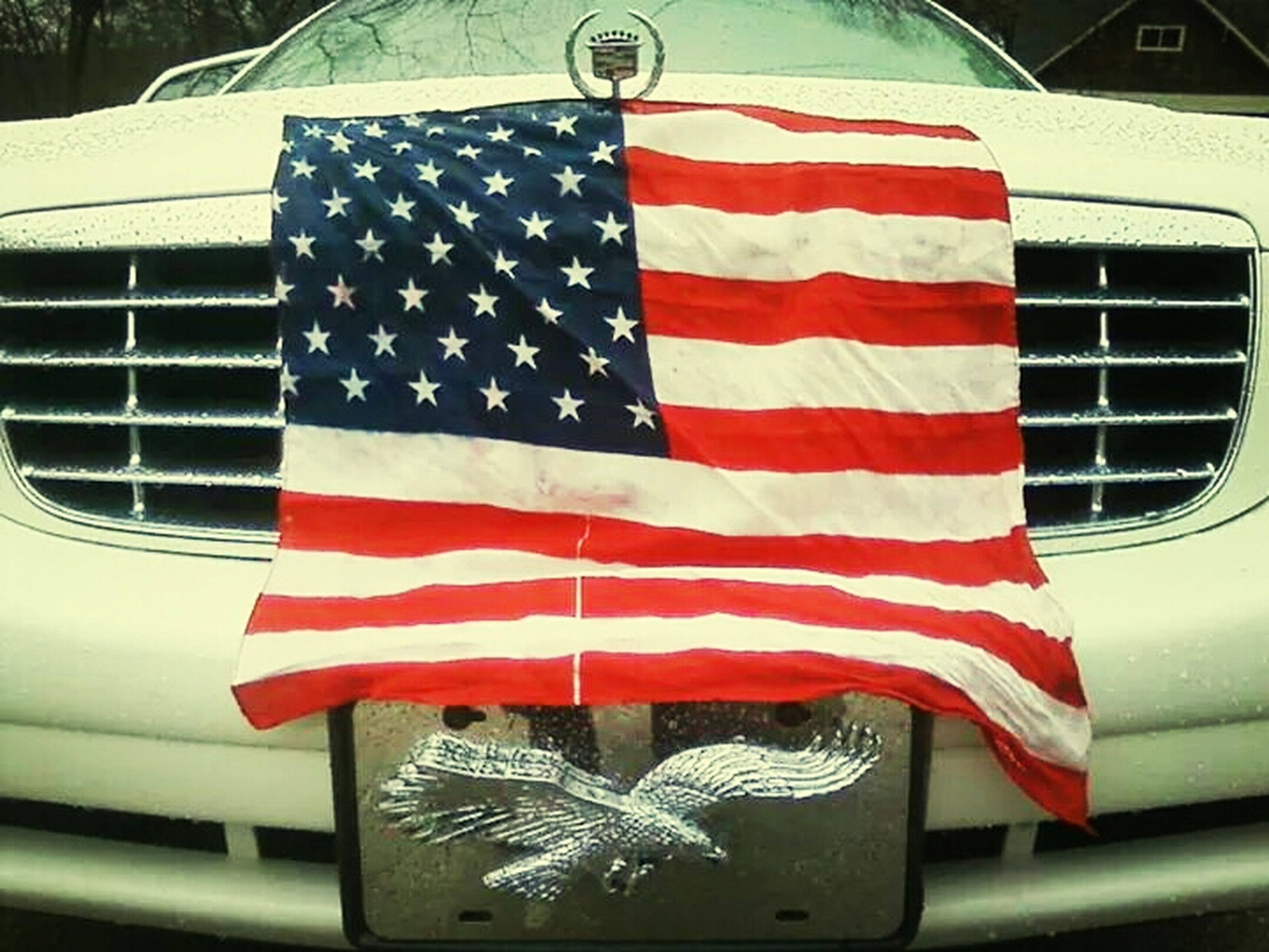 patriotism, american flag, flag, national flag, identity, striped, red, transportation, culture, star shape, white color, pride, mode of transport, car, day, road marking, wind, pole, low angle view, no people