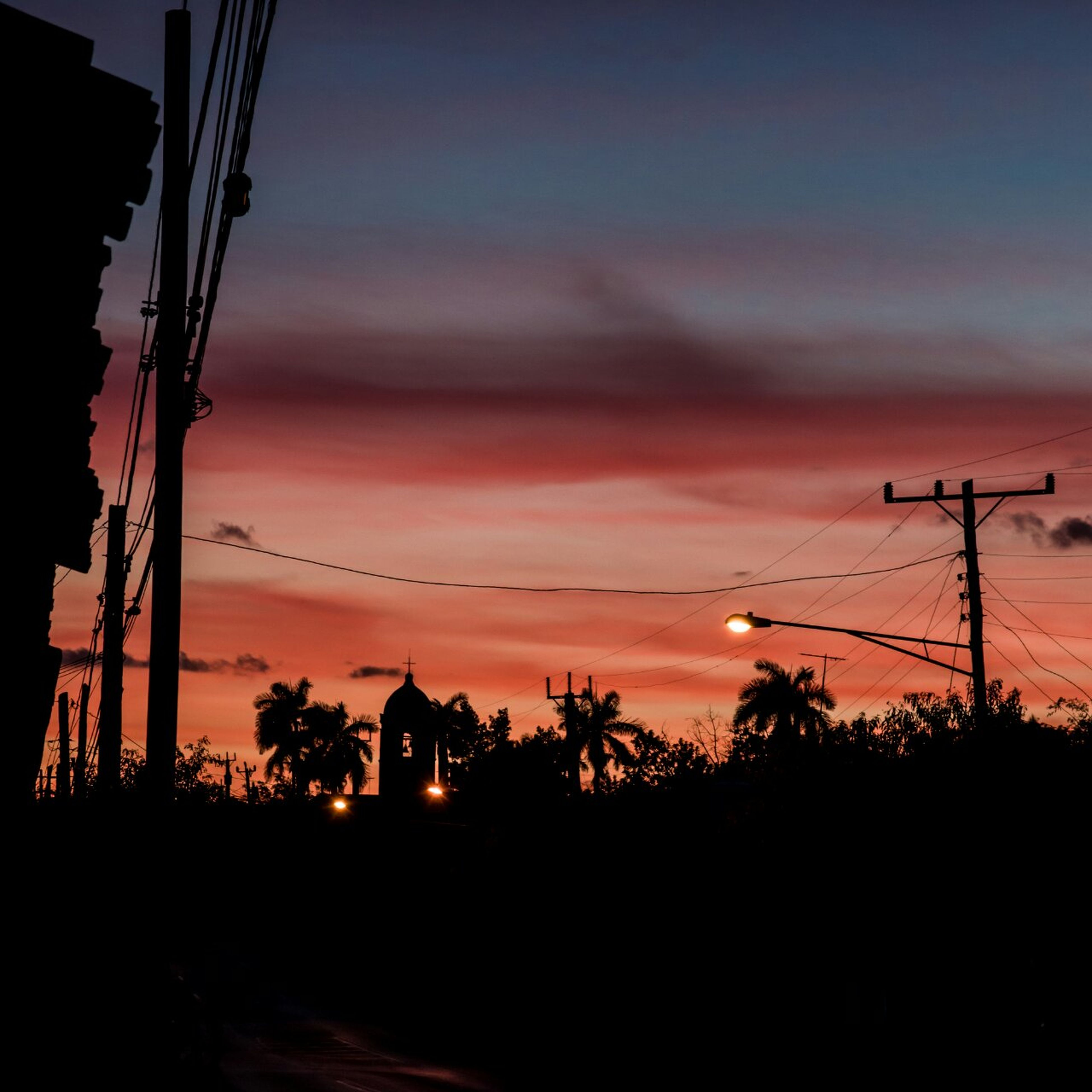sunset, silhouette, power line, electricity pylon, orange color, sky, power supply, electricity, fuel and power generation, cable, connection, beauty in nature, nature, tree, scenics, tranquility, technology, tranquil scene, dusk, cloud - sky