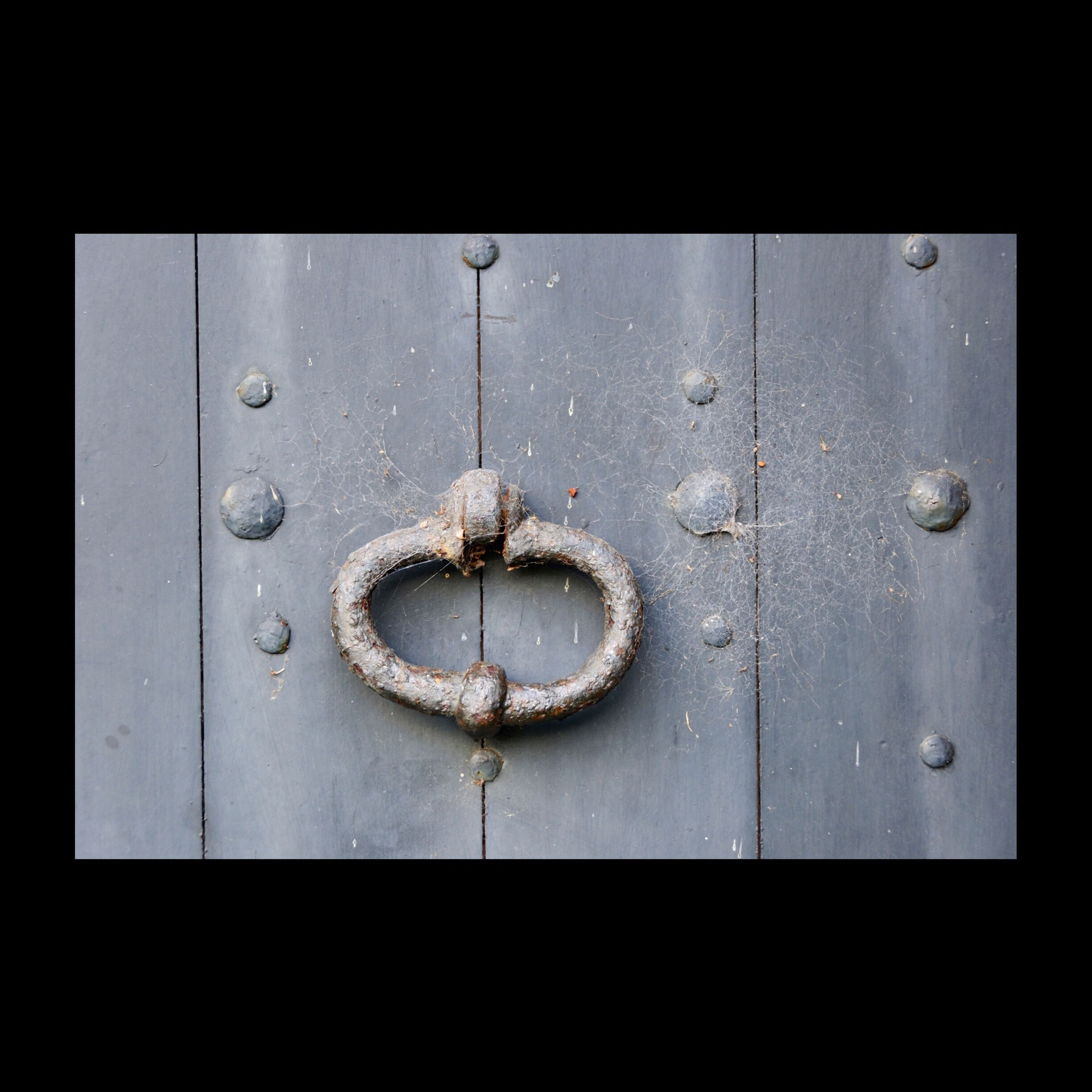 door, indoors, close-up, metal, safety, protection, closed, security, full frame, backgrounds, built structure, wall - building feature, circle, metallic, wood - material, pattern, no people, old, hanging, architecture