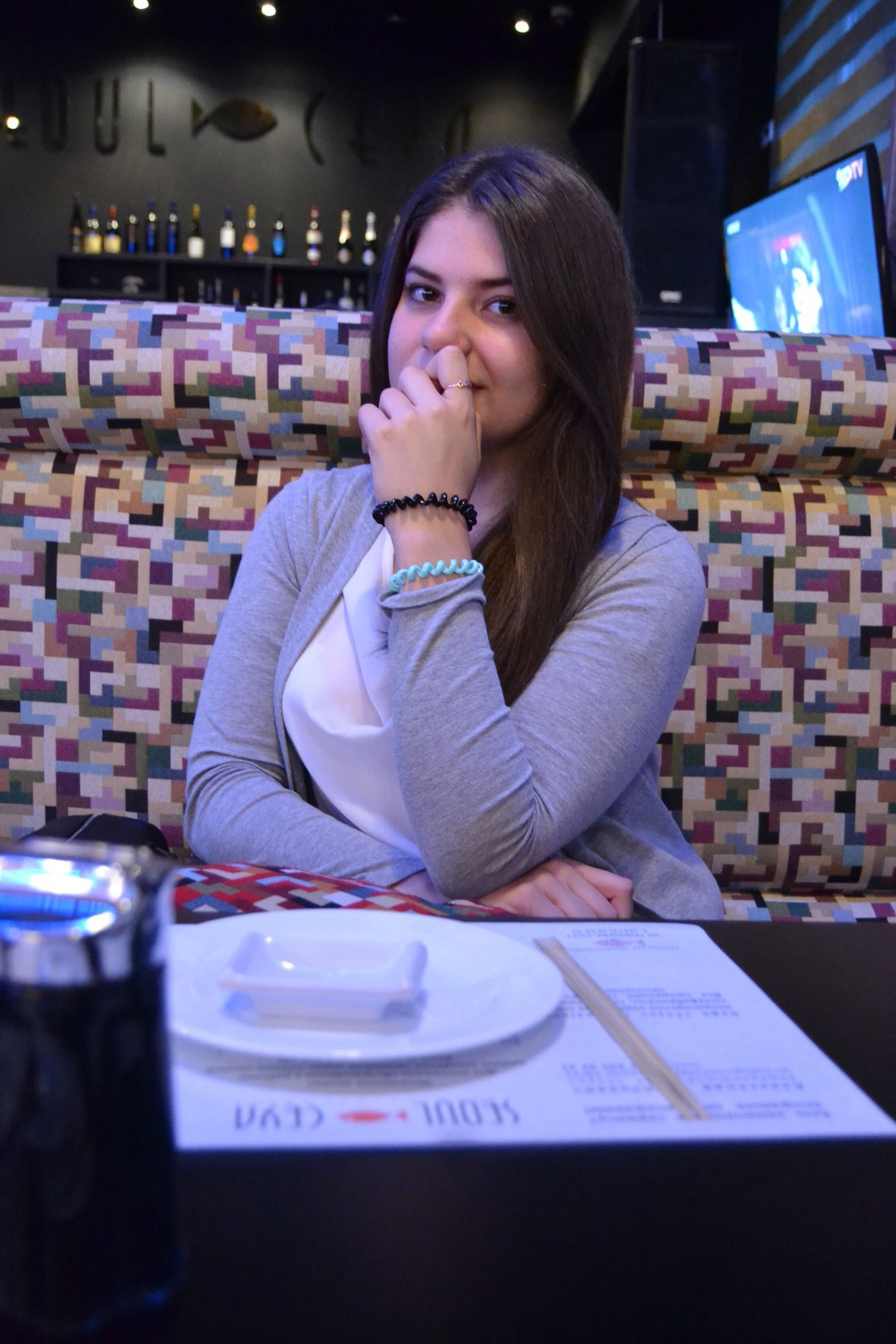 food and drink, indoors, young adult, lifestyles, drink, person, casual clothing, leisure activity, refreshment, front view, table, sitting, portrait, restaurant, looking at camera, waist up, holding, freshness