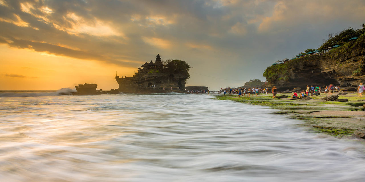 Sunset at Tanah Lot, a popular tourist attraction in Bali, Indonesia. Architecture Bali Beach Clouds Clouds And Sky Cloudscape INDONESIA Island Landscape Moss Nature Outdoors Pura Rock Formation Social Issues Sunset Sunsets Tanah Lot Temple Tourist Tourist Attraction  Travel Travel Destinations Water Waves
