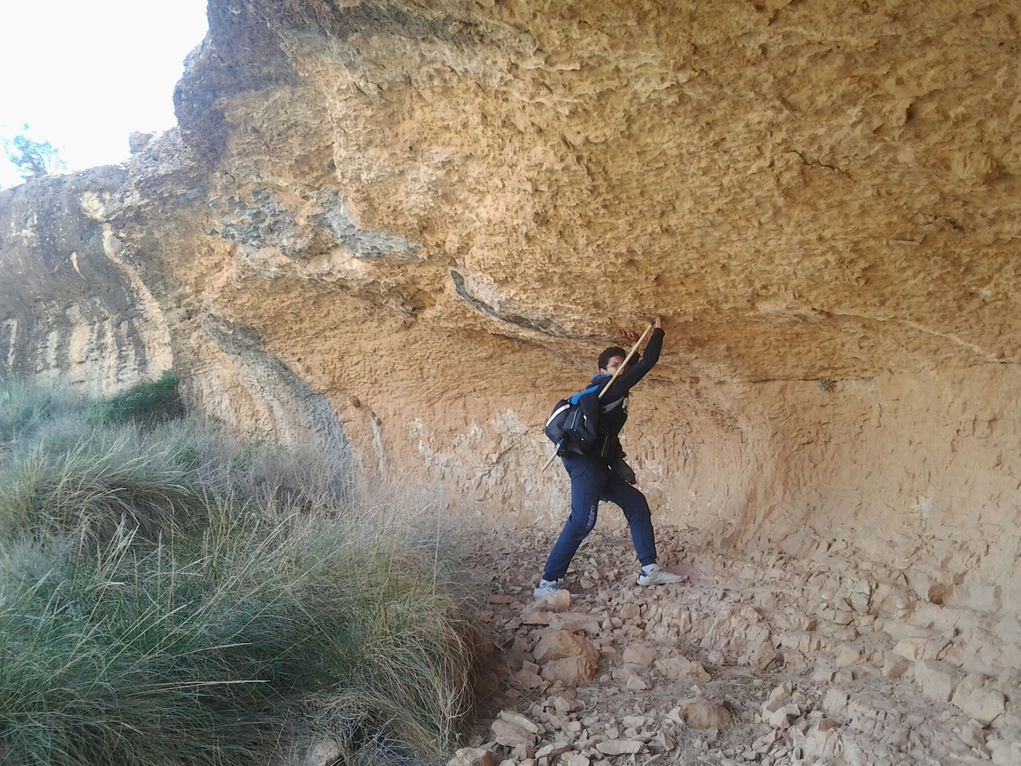 full length, one animal, rock - object, adventure, nature, standing, animal themes, mountain, sunlight, side view, day, leisure activity, outdoors, lifestyles, rock formation, landscape, men, motion