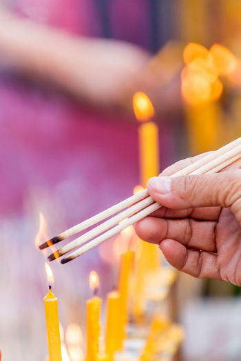 People are lighting incense stick to pray for goodness Buddhism; Burning Candle Close-up Culture; Day Fire Flame Focus On Foreground Goodness; Heat - Temperature Holding Human Hand Incense-sticks; Incense; Indoors  Merit; Mist; One Person People Pray; Real People Religion; Smoke; Tradition;