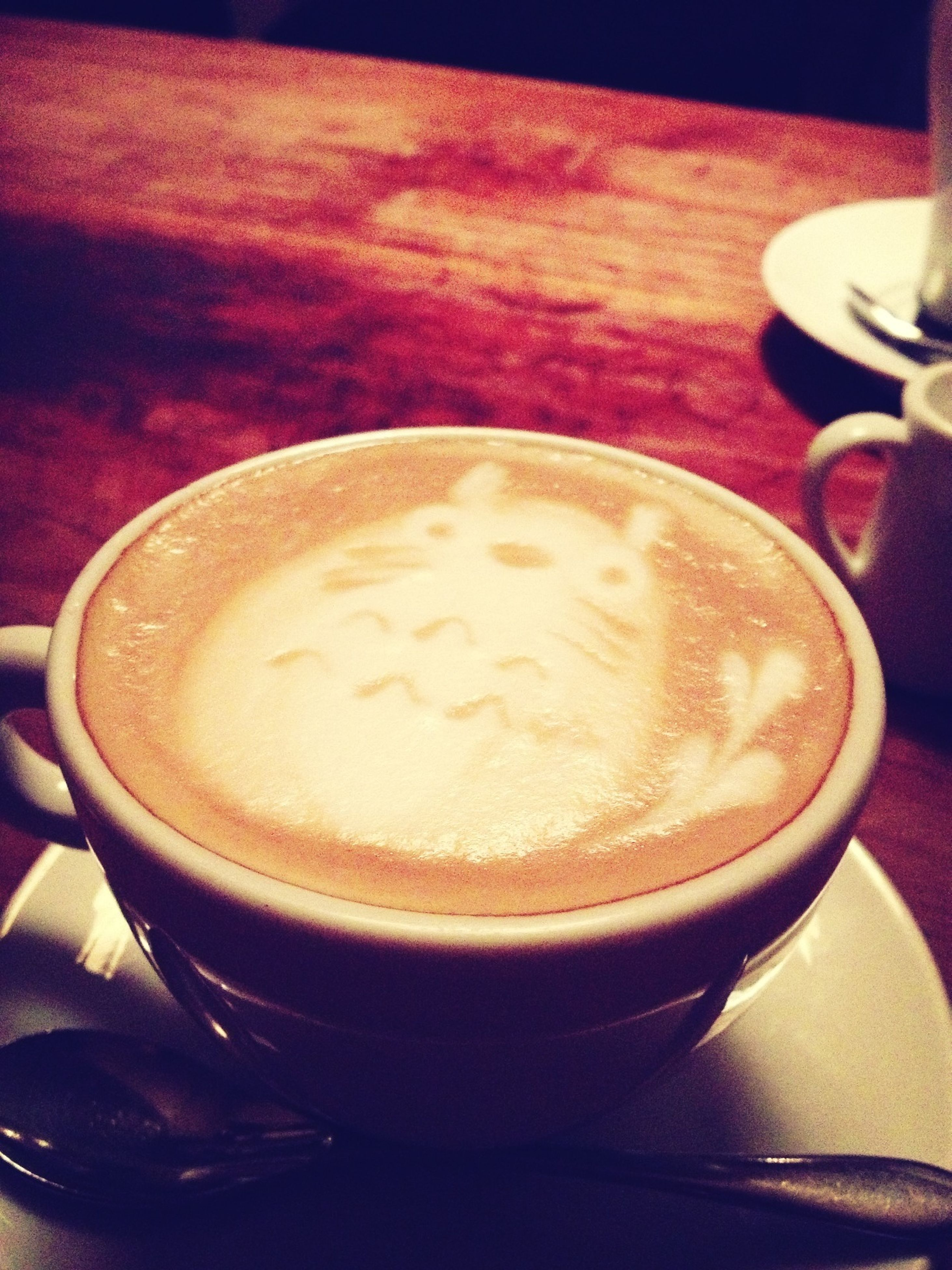 drink, food and drink, coffee cup, refreshment, indoors, frothy drink, coffee - drink, table, cappuccino, saucer, freshness, close-up, still life, coffee, froth art, cup, spoon, beverage, high angle view, no people