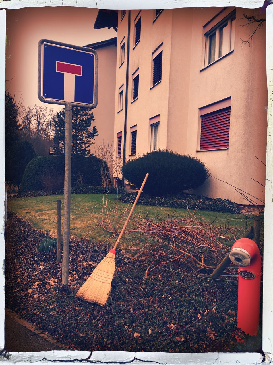 Road Sign And Broom Outside Building In City
