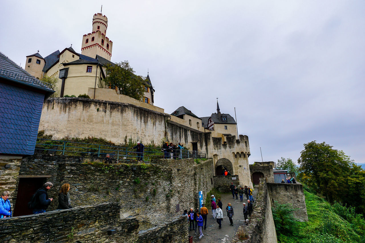 architecture, built structure, building exterior, sky, low angle view, day, real people, history, outdoors, cloud - sky, travel destinations, castle, large group of people, nature, men, people