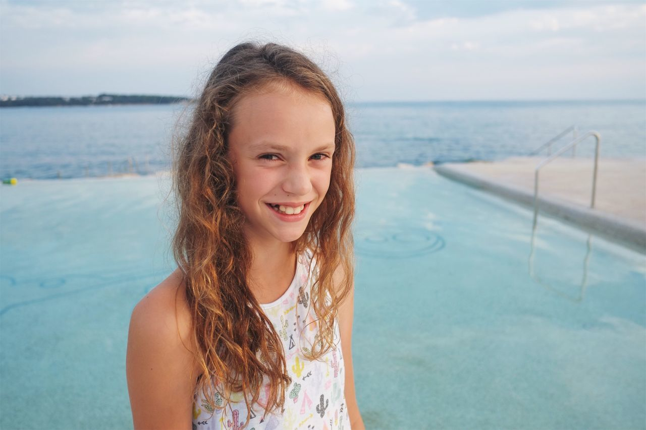Happy girl at the swimming pool. Water Sea One Person Real People Young Adult Looking At Camera Smiling Young Women Horizon Over Water Portrait Outdoors Standing Leisure Activity Nature Long Hair Front View Happiness Day Scenics Lifestyles Authentic Moments Swimming Pool Summer Holiday Seaside