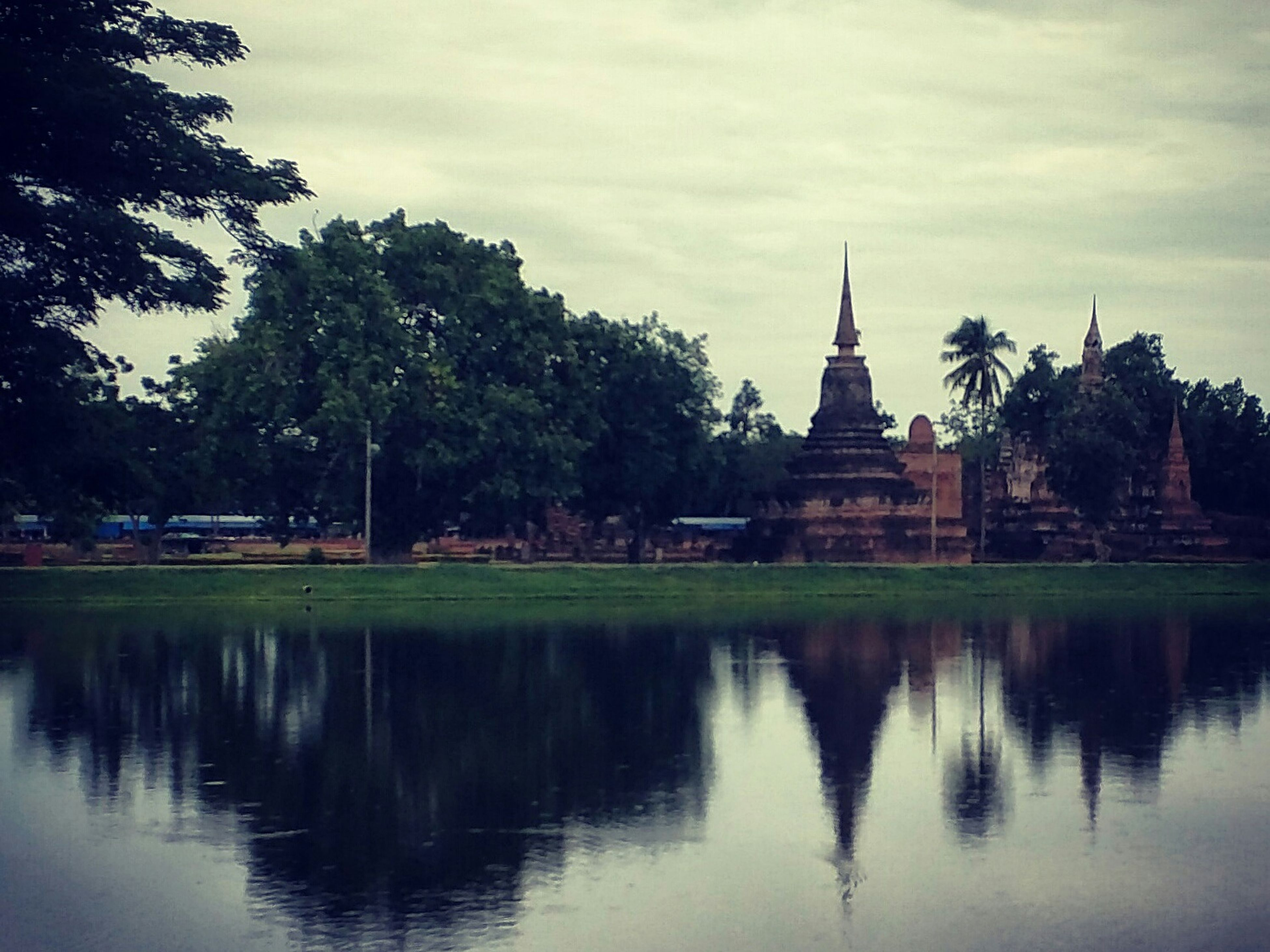 architecture, built structure, building exterior, tree, reflection, water, waterfront, sky, lake, religion, place of worship, spirituality, cloud - sky, river, travel destinations, famous place, cloud, church, pond
