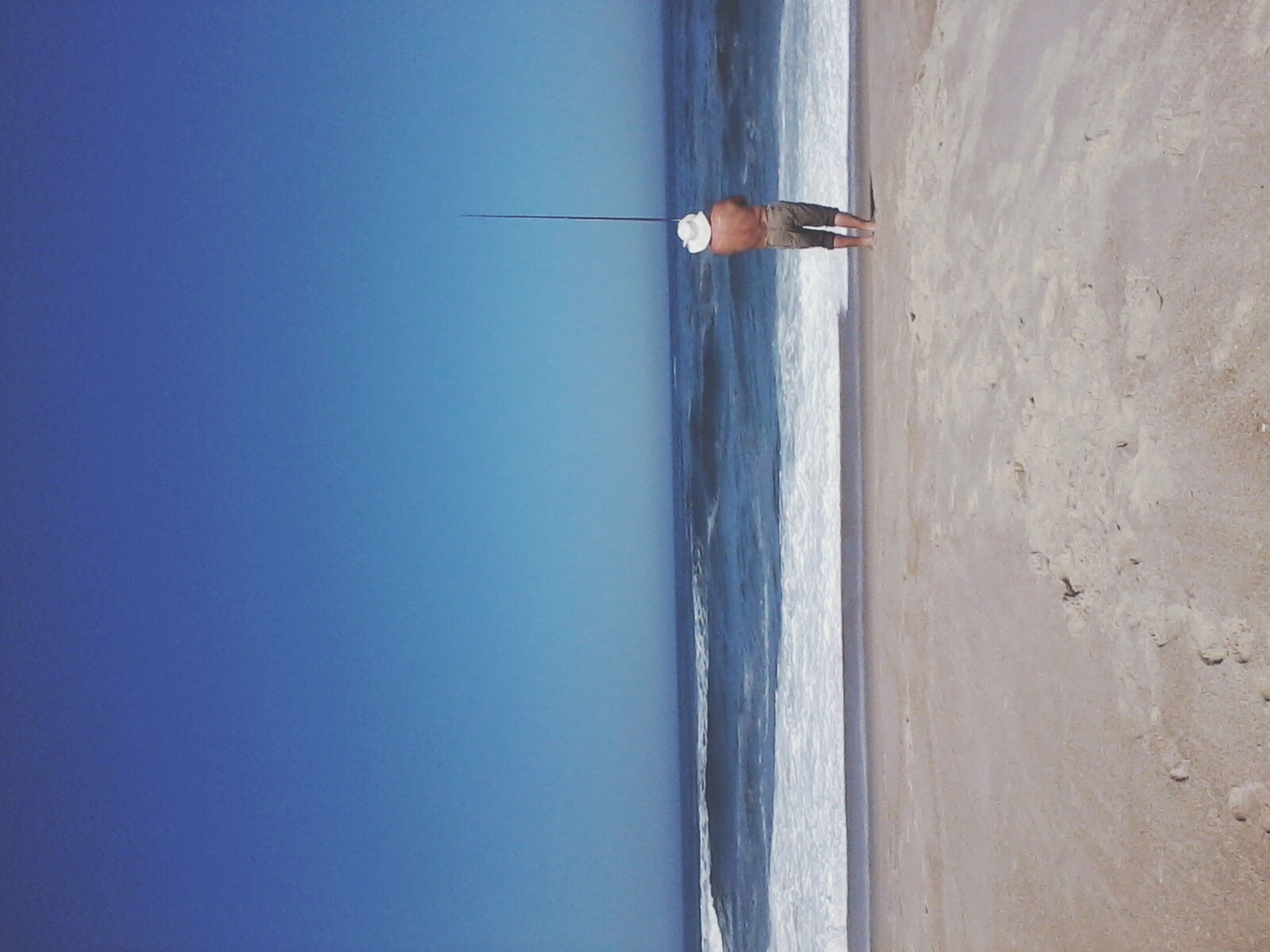 sea, horizon over water, copy space, water, beach, blue, clear sky, tranquil scene, tranquility, one person, scenics, shore, nature, beauty in nature, day, sky, sand, full length, idyllic, bird