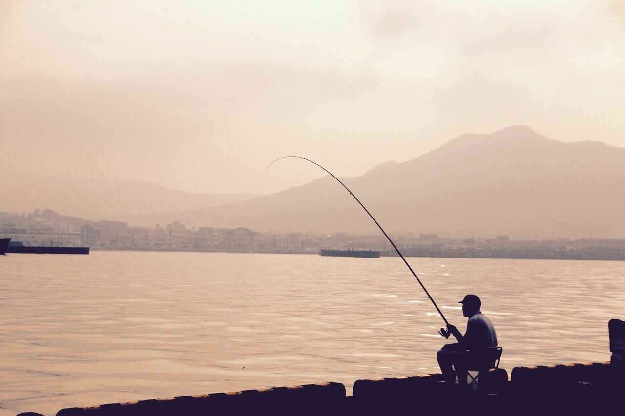 fishing, fishing rod, fishing pole, water, real people, fishing tackle, one person, weekend activities, men, nature, tranquil scene, ocean, silhouette, holding, standing, rear view, sitting, leisure activity, outdoors, tranquility, beauty in nature, scenics, sunset, sky, day, adult, people