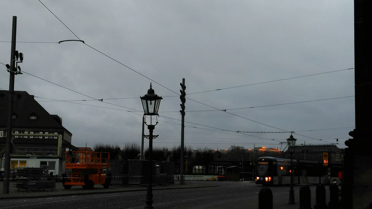cable, power line, transportation, connection, electricity, electricity pylon, sky, power supply, car, mode of transport, outdoors, land vehicle, fuel and power generation, built structure, no people, technology, day