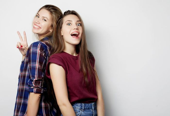 Adult Adults Only Beautiful Woman Blond Hair Bonding Cheerful Enjoyment Friendship Fun Happiness Human Body Part Looking At Camera Mouth Open Only Young Women People Portrait Smiling Standing Studio Shot Togetherness Toothy Smile Two People White Background Young Adult Young Women