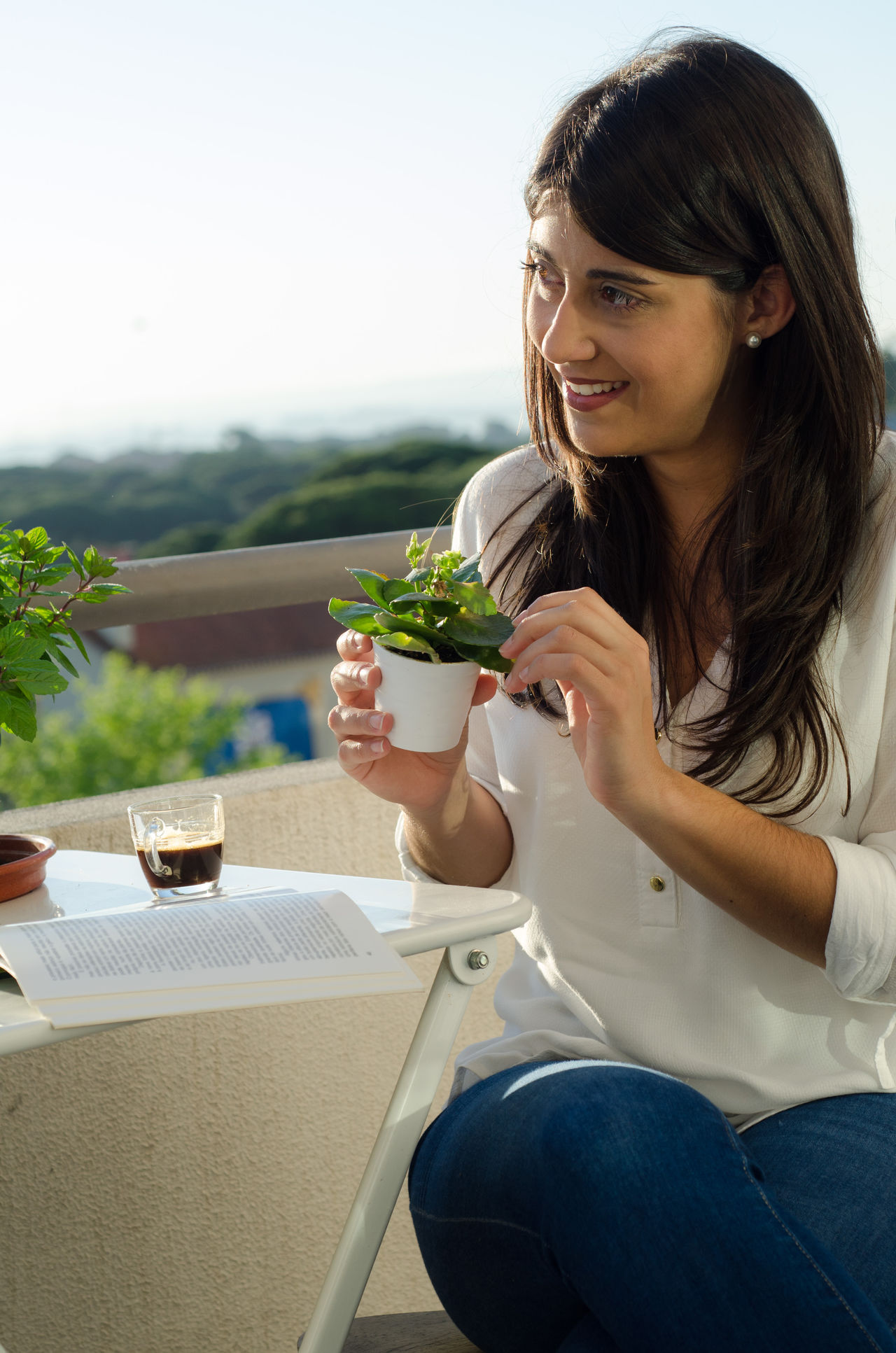 Women reading a book in the morning Day Green Greenery Hanging Out Jeans Morning One Person People Plant Real People Serious Sitting Smile Women Young Women