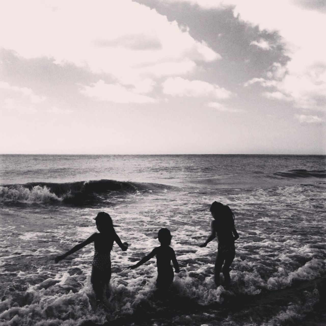 Silhouette Girls Playing On Waves At Shore