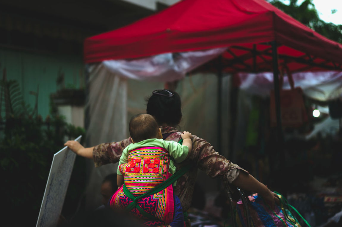 Luang Prabang, Laos Mother Mother And Daughter Baby Carrier Carrying Baby On Back Carrying Belongings Copine Focus On Foreground Handling Hands Full Laos Laos Street Laos Street Photo Laos Street Photography Laos Street Scene Laotian Streets Luang Prabang Luang Prabang Old Quarter Mother And Child Rear View Street Photography Street Scene Women