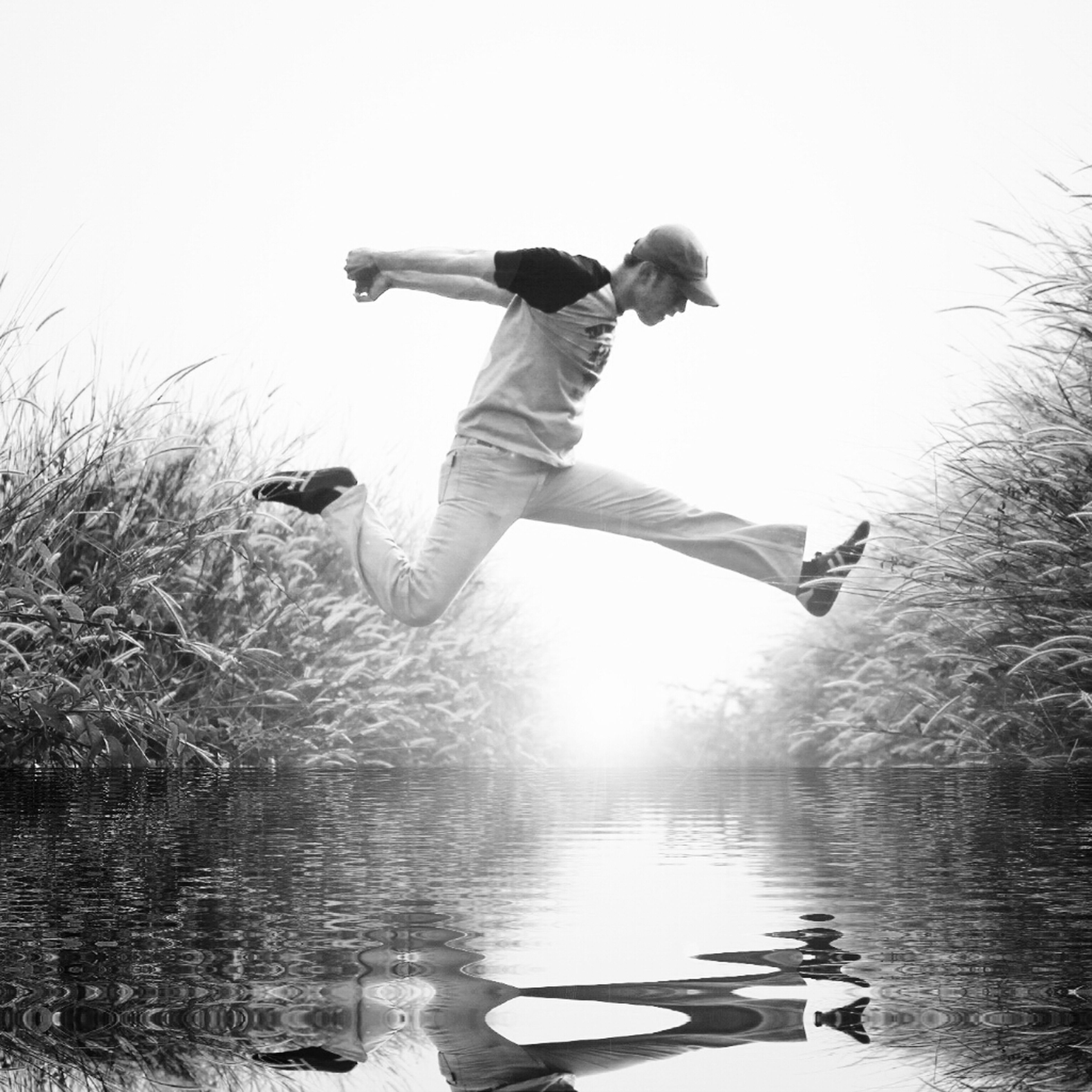 water, lifestyles, full length, leisure activity, mid-air, lake, jumping, waterfront, reflection, clear sky, arms outstretched, nature, tree, men, casual clothing, young adult, river, tranquility