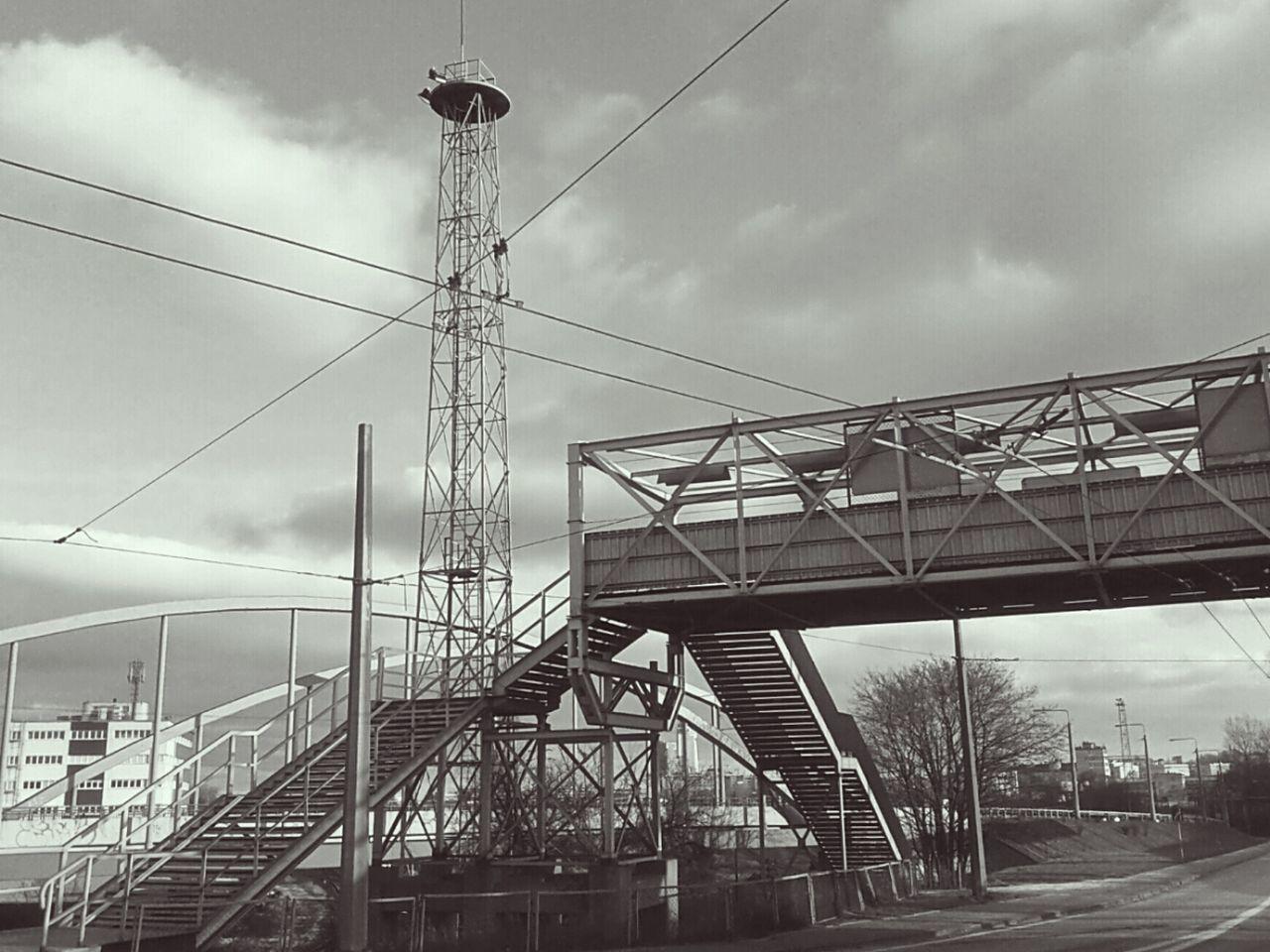 Low Angle View Of Pedestrian Walkway Bridge Against Cloudy Sky