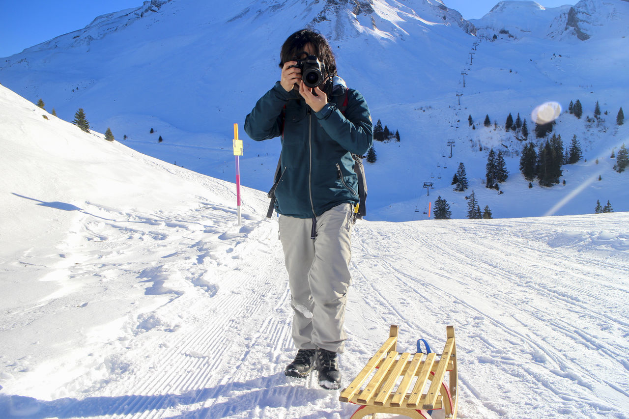 Man Photographing On Snow Covered Mountains