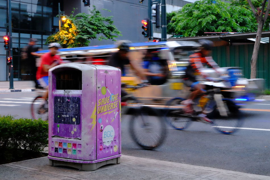 Bicycle Blurred Motion City City Life City Street Cyclist Day Focus On Foreground Garbage Garbage Can Incidental People Jeepney Land Vehicle Mode Of Transport Motion Outdoors Parked Parking Road Segregation  Stationary Street Taxi Transportation