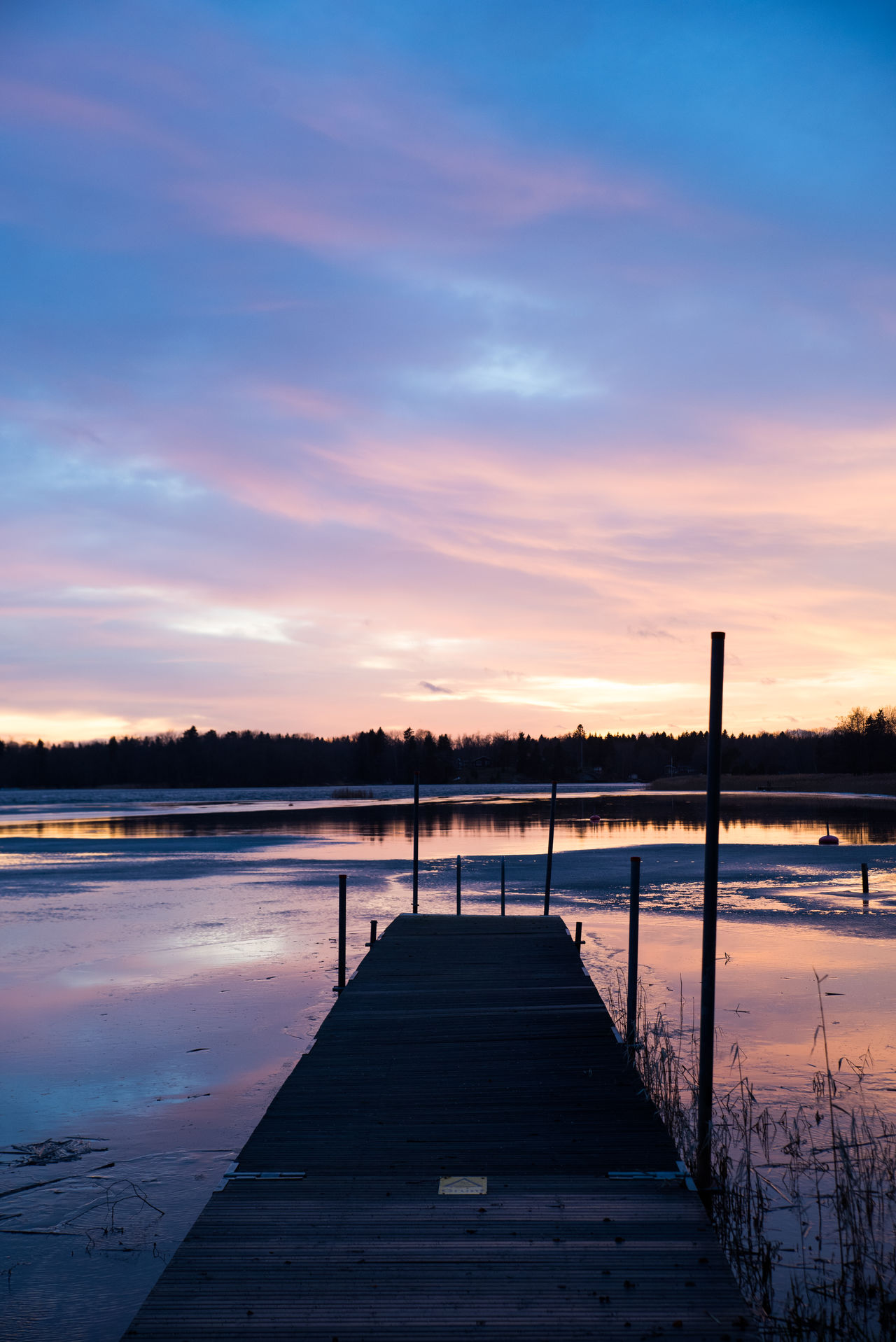 The sun has just set behind the trees and the sky is filled with orange and purple tones. Beauty In Nature Cloud - Sky Day Jetty Lake Nature No People Outdoors Scenics Sky Sunset Tranquil Scene Tranquility Tree Water
