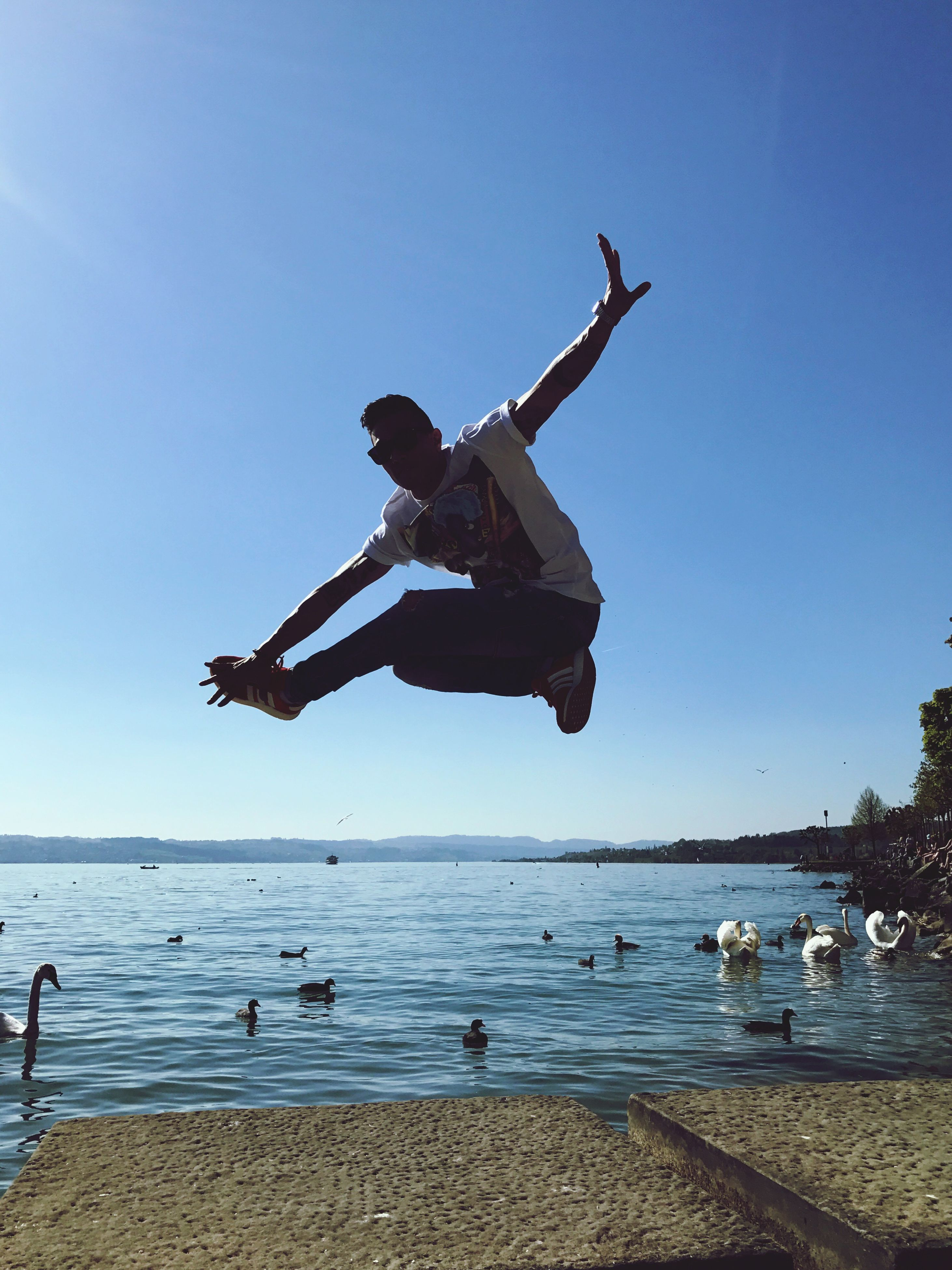 mid-air, jumping, beach, full length, sea, young adult, motion, men, real people, outdoors, clear sky, fun, sky, happiness, water, one person, day, sand, horizon over water, adult, cheerful, people, one man only, only men, adults only