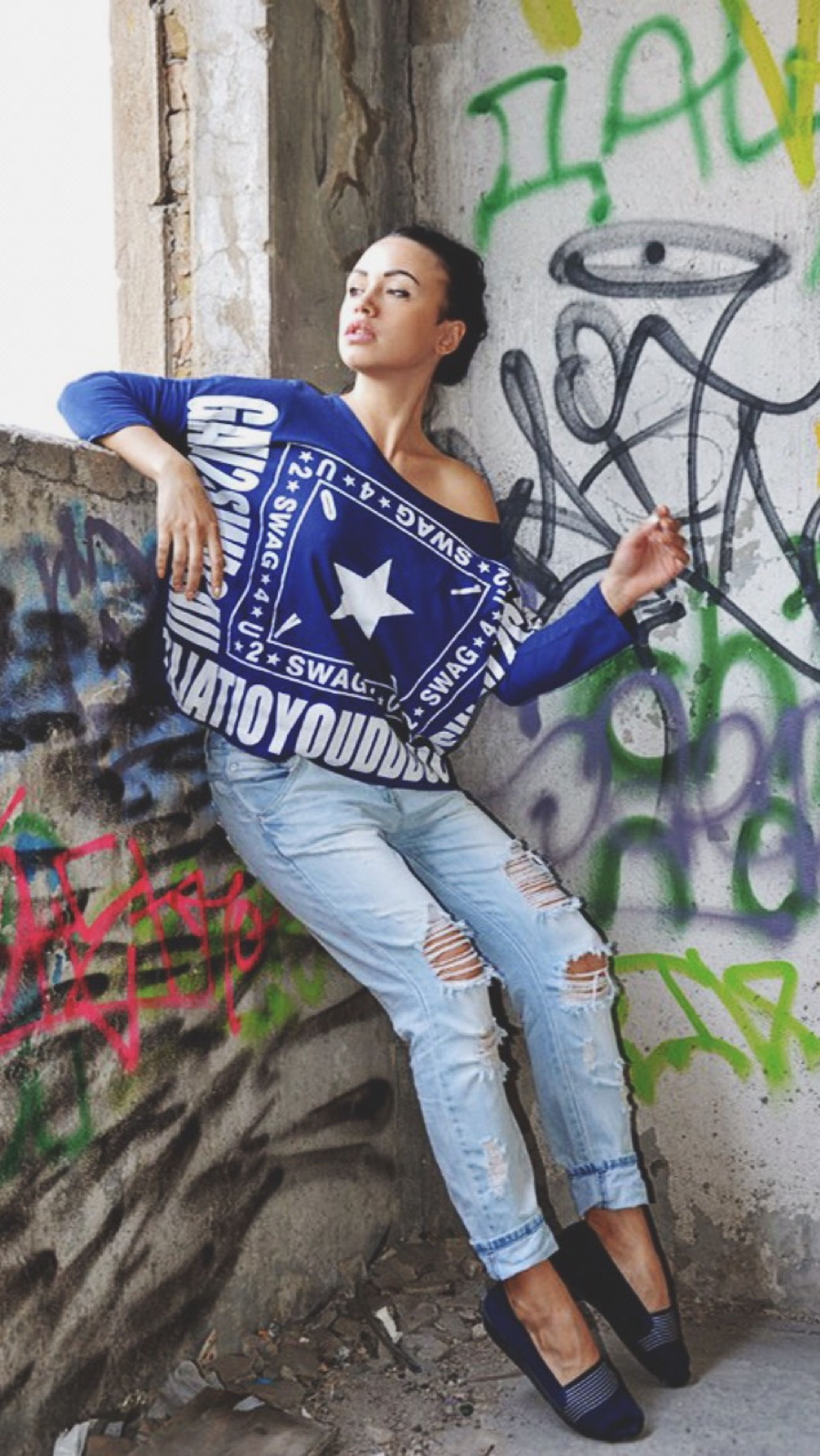 casual clothing, young adult, lifestyles, front view, person, leisure activity, looking at camera, full length, standing, portrait, wall - building feature, young women, built structure, smiling, graffiti, fashion, three quarter length, outdoors