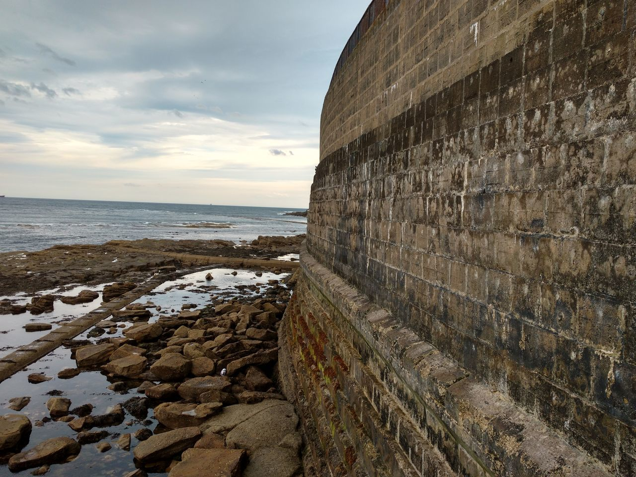 sea, water, horizon over water, sky, nature, cloud - sky, scenics, tranquility, built structure, outdoors, day, architecture, beauty in nature, tranquil scene, travel destinations, no people, beach, groyne