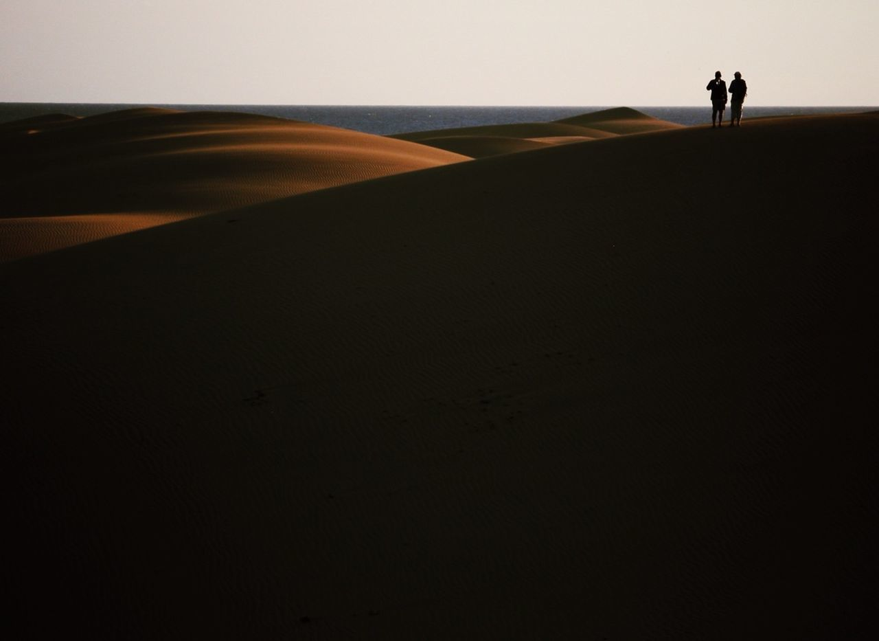 Rear view of two silhouette people standing on sandy beach