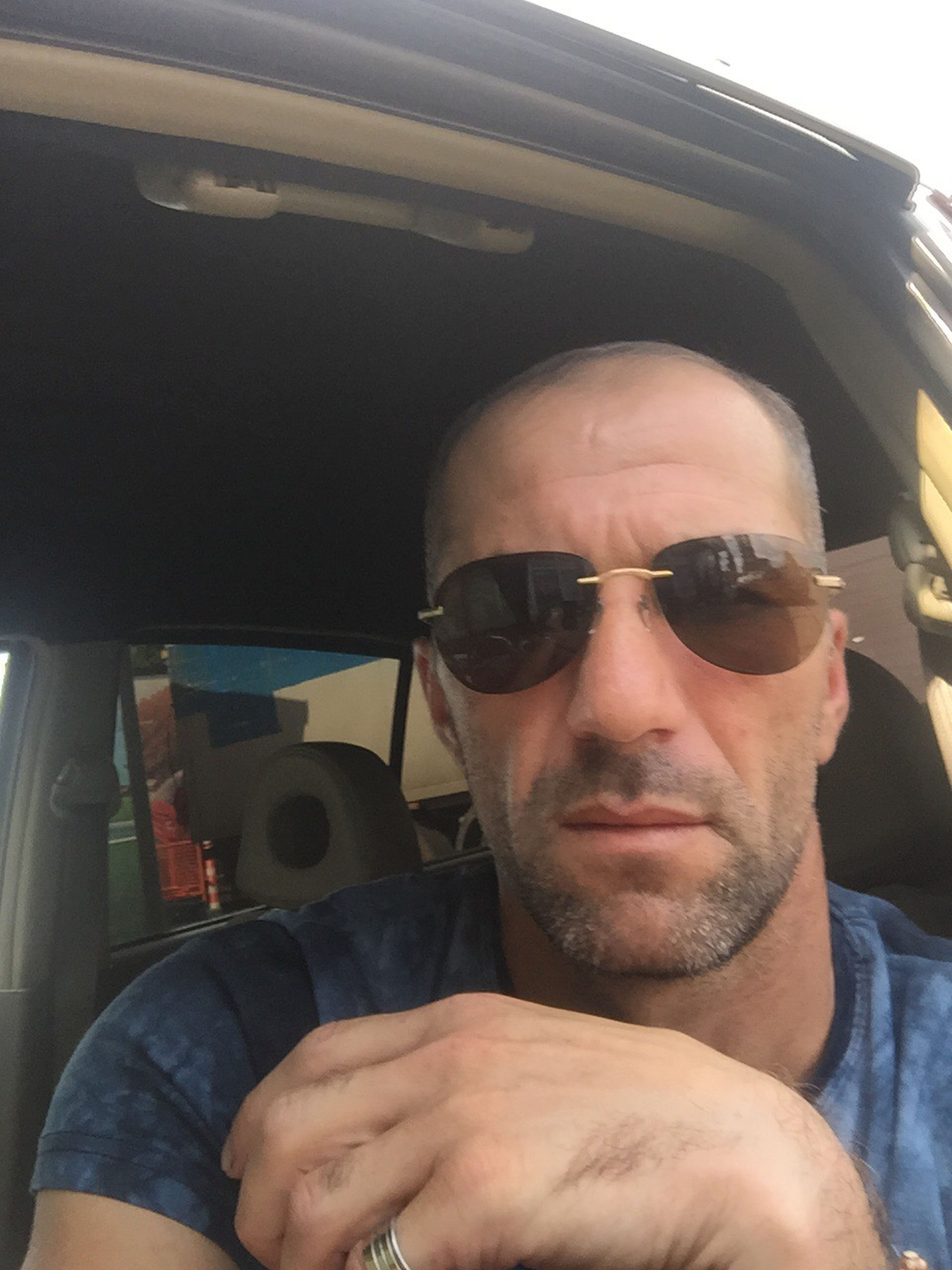 transportation, headshot, sunglasses, mode of transport, lifestyles, young men, travel, leisure activity, close-up, car interior, front view, looking at camera, casual clothing, young adult, relaxation, person, focus on foreground