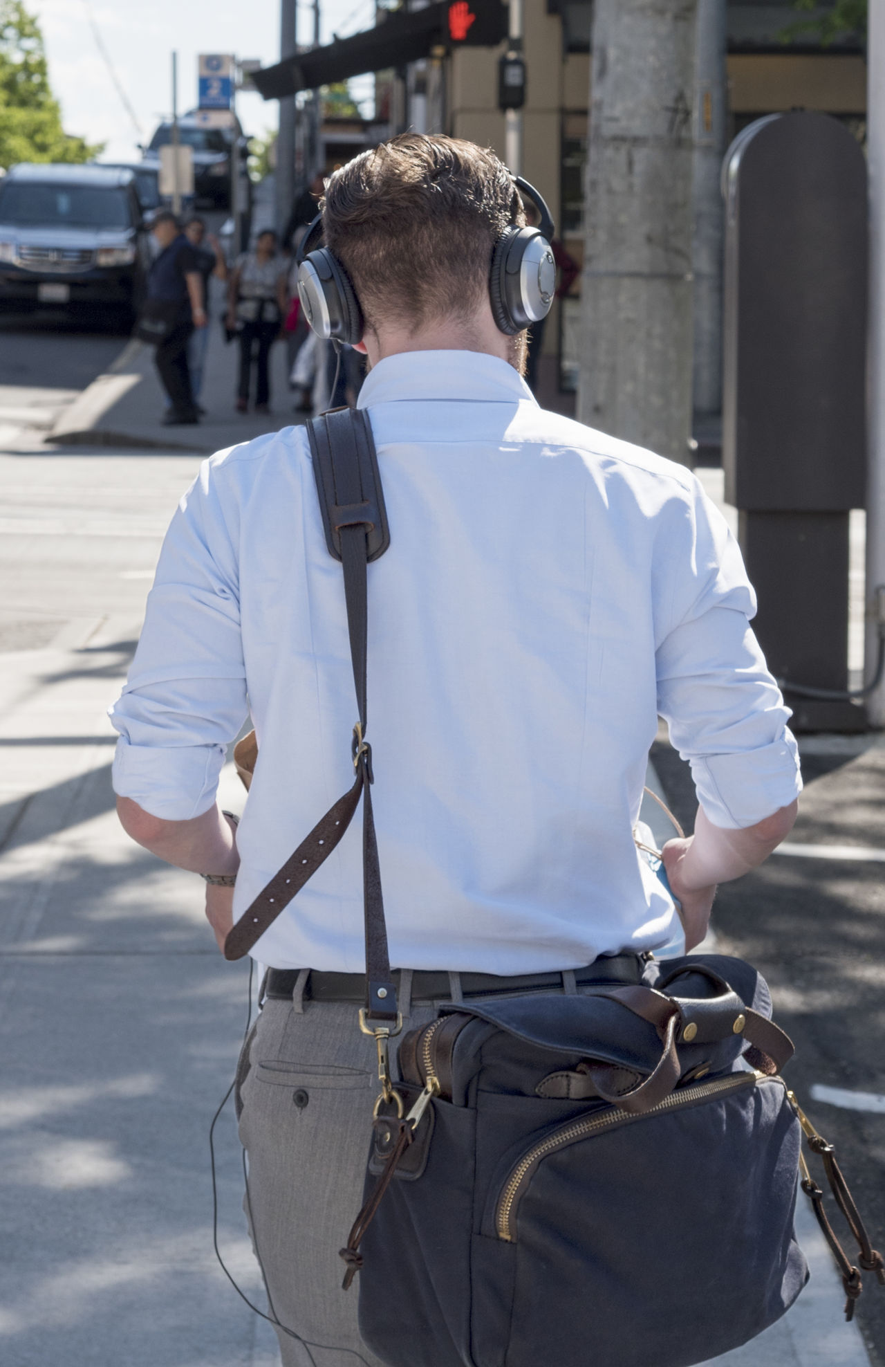 Businessman on the go in the city wearing headphones carrying shoulder bag Architecture Belt  Businessman Commute Day Headphones Holding Leisure Activity Lifestyles Men Occupation One Person Outdoors People Real People Rear View Rear View Shoulder Bag Standing Technology Three Quarter Length Urban Walking Wireless Technology Young Adult