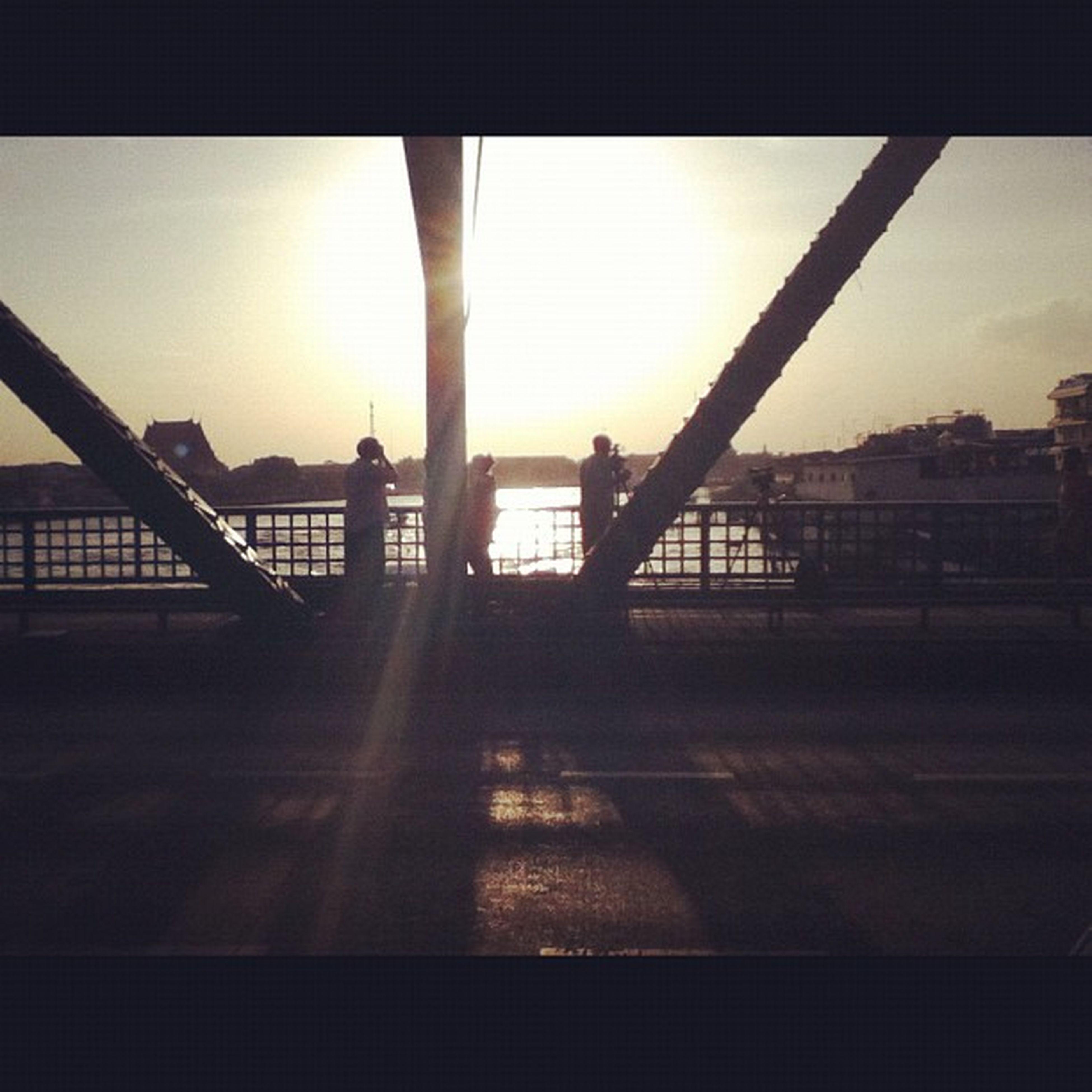 sunset, silhouette, sun, water, sunlight, built structure, sky, architecture, orange color, bridge - man made structure, reflection, railing, sunbeam, transportation, lens flare, nature, river, sea, outdoors, bridge