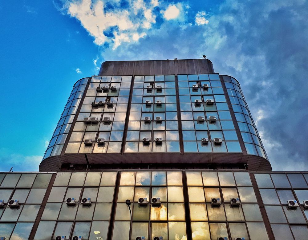 Reflections Low Angle View Sky Architecture Built Structure Day Building Exterior Window Cloud - Sky No People Outdoors Blue Skyscraper Mirrored VSCO PRISHTINA Vscokosova Architecture Low Angle View Antenna - Aerial Reflection