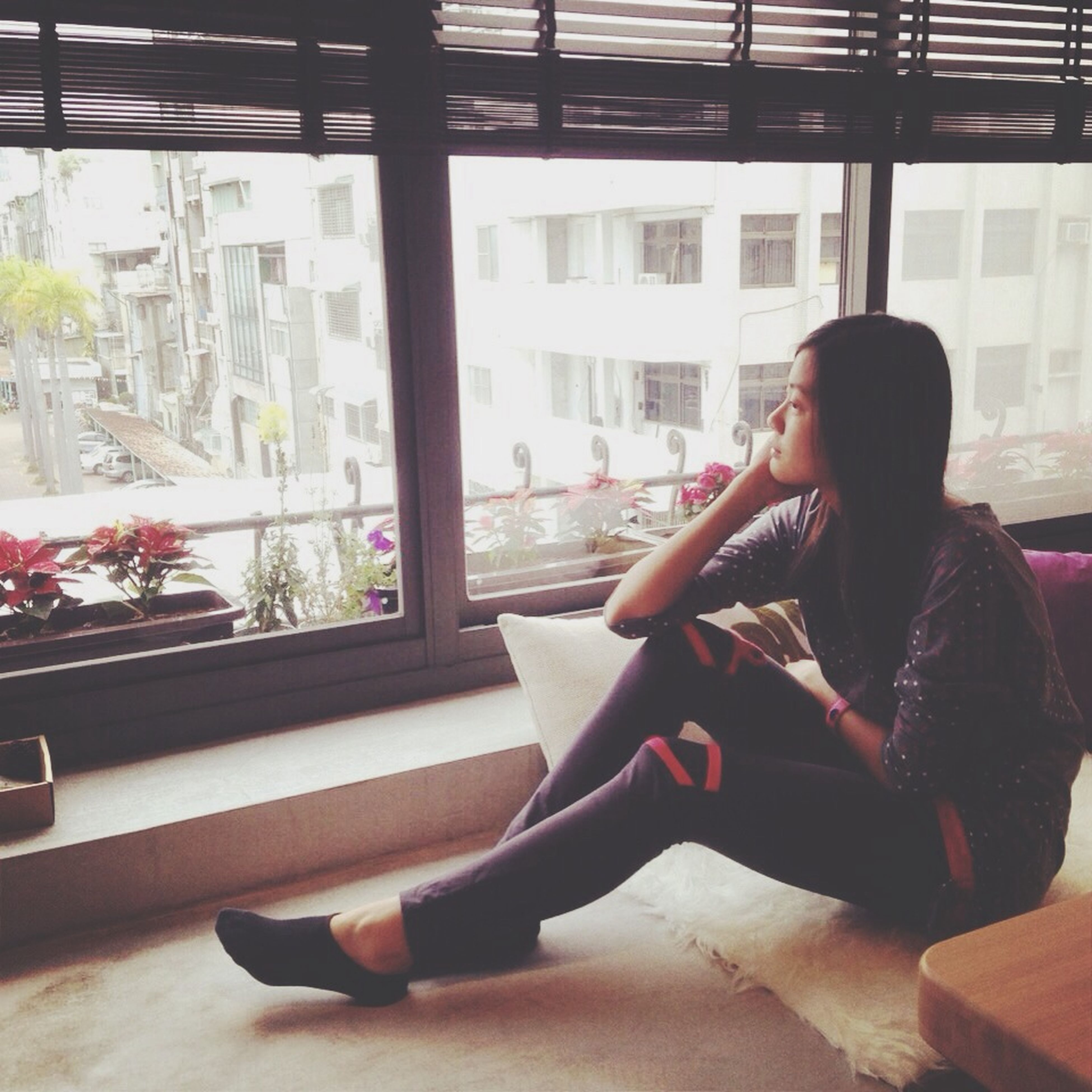 sitting, indoors, lifestyles, window, leisure activity, relaxation, young adult, person, glass - material, young women, chair, transparent, looking through window, side view, architecture, transportation, casual clothing, built structure
