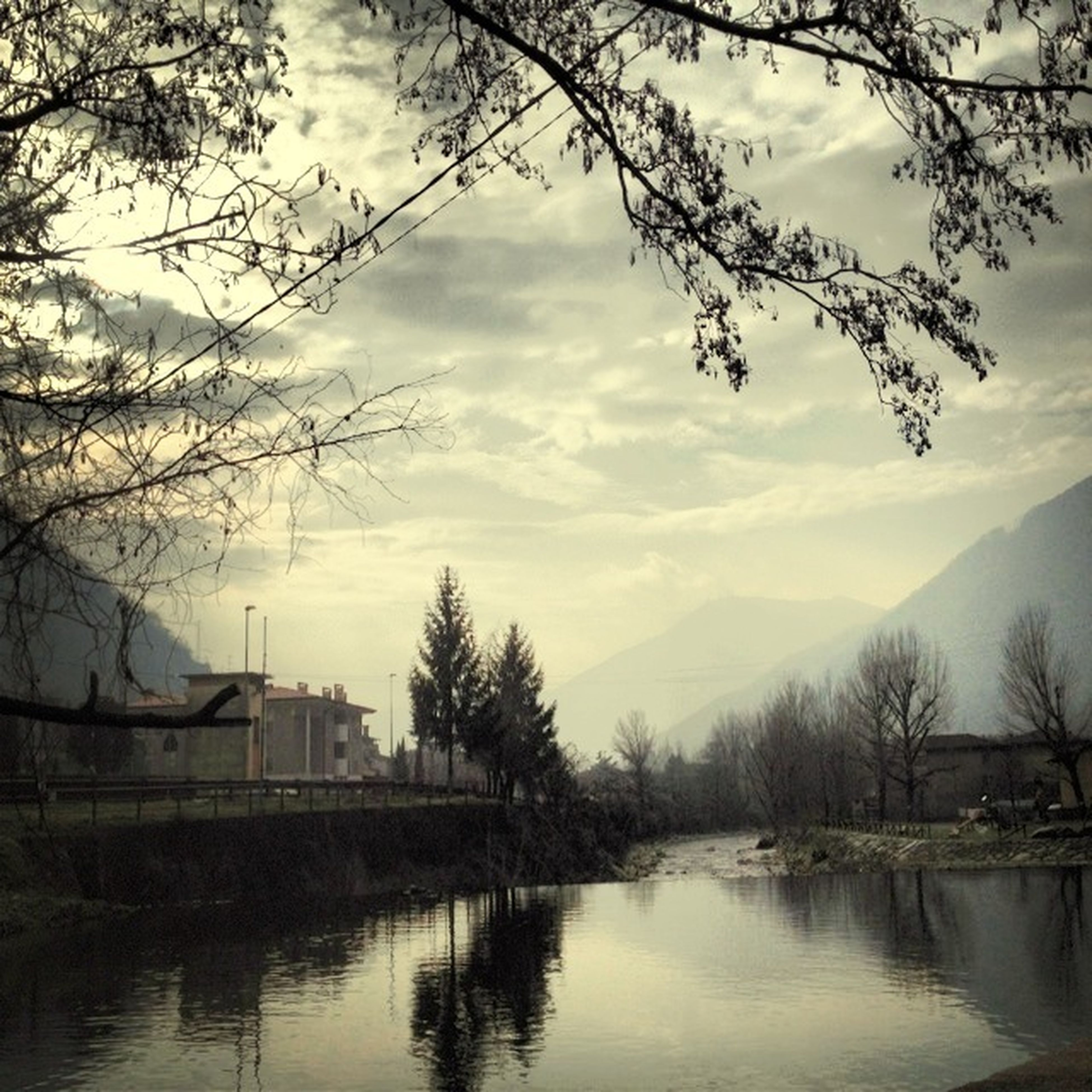 water, sky, tree, lake, cloud - sky, waterfront, bare tree, built structure, reflection, cloud, tranquility, building exterior, river, tranquil scene, architecture, scenics, nature, beauty in nature, cloudy, branch