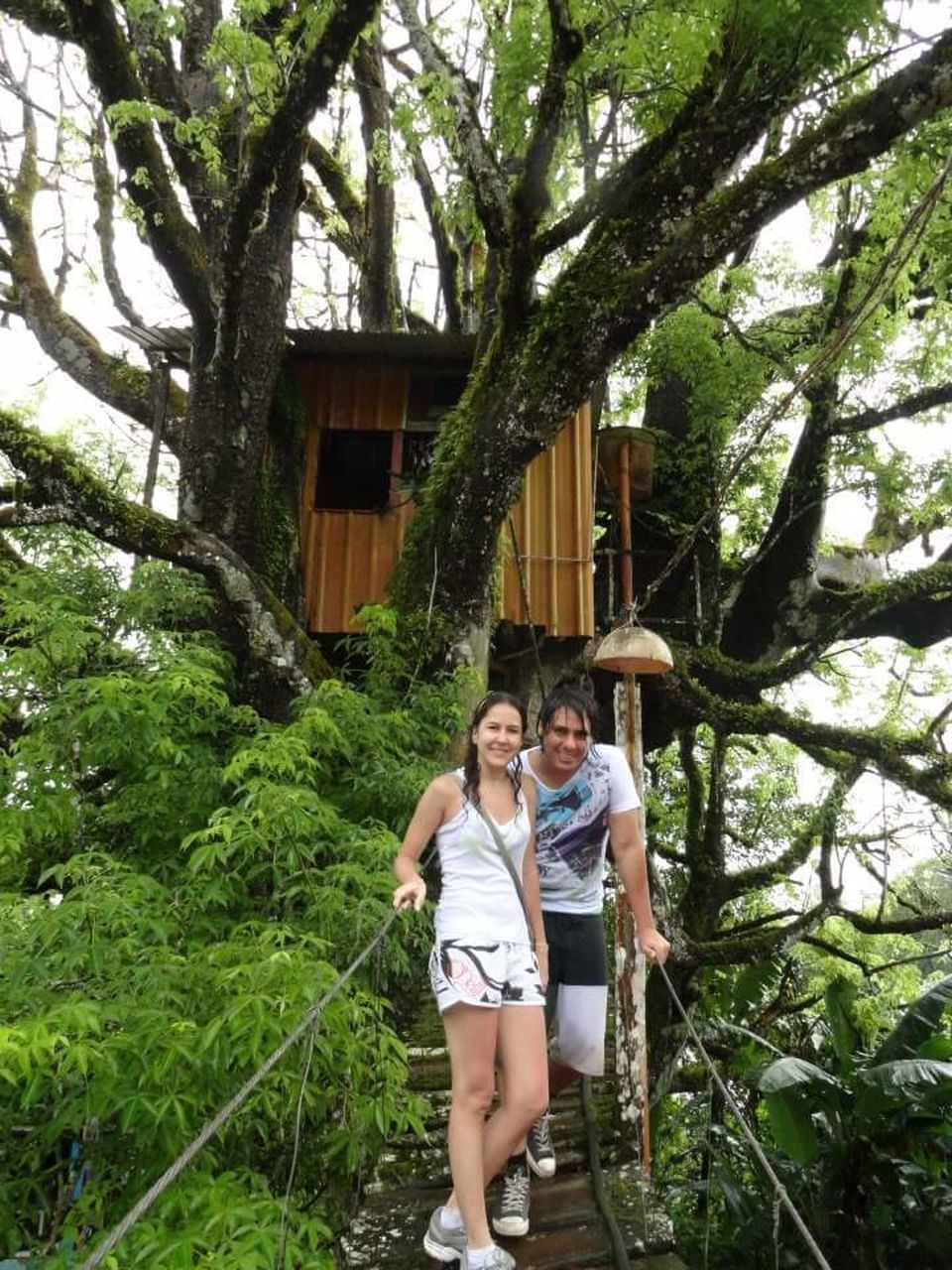 two people, tree, togetherness, young adult, young women, day, outdoors, leisure activity, heterosexual couple, front view, casual clothing, vacations, smiling, standing, happiness, love, adults only, bonding, branch, plant, full length, cheerful, nature, people, adult, building exterior, architecture