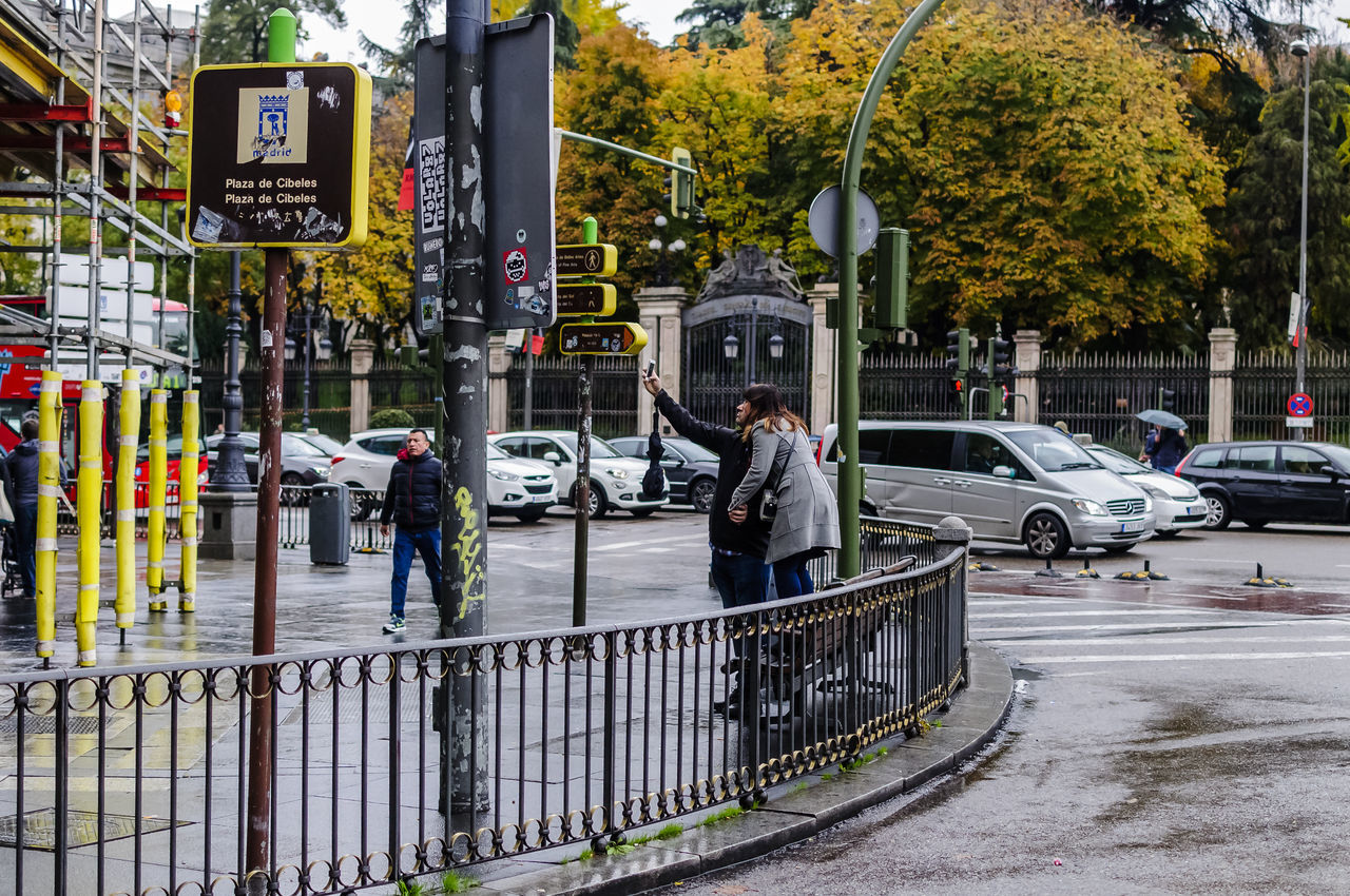 A couple taking a selfie in Cibeles after a shower. Adult Architecture Cibeles City City Street Day Editorial  General View Outdoors People Road Sign Selfie Street Photography Street View Tree Wet