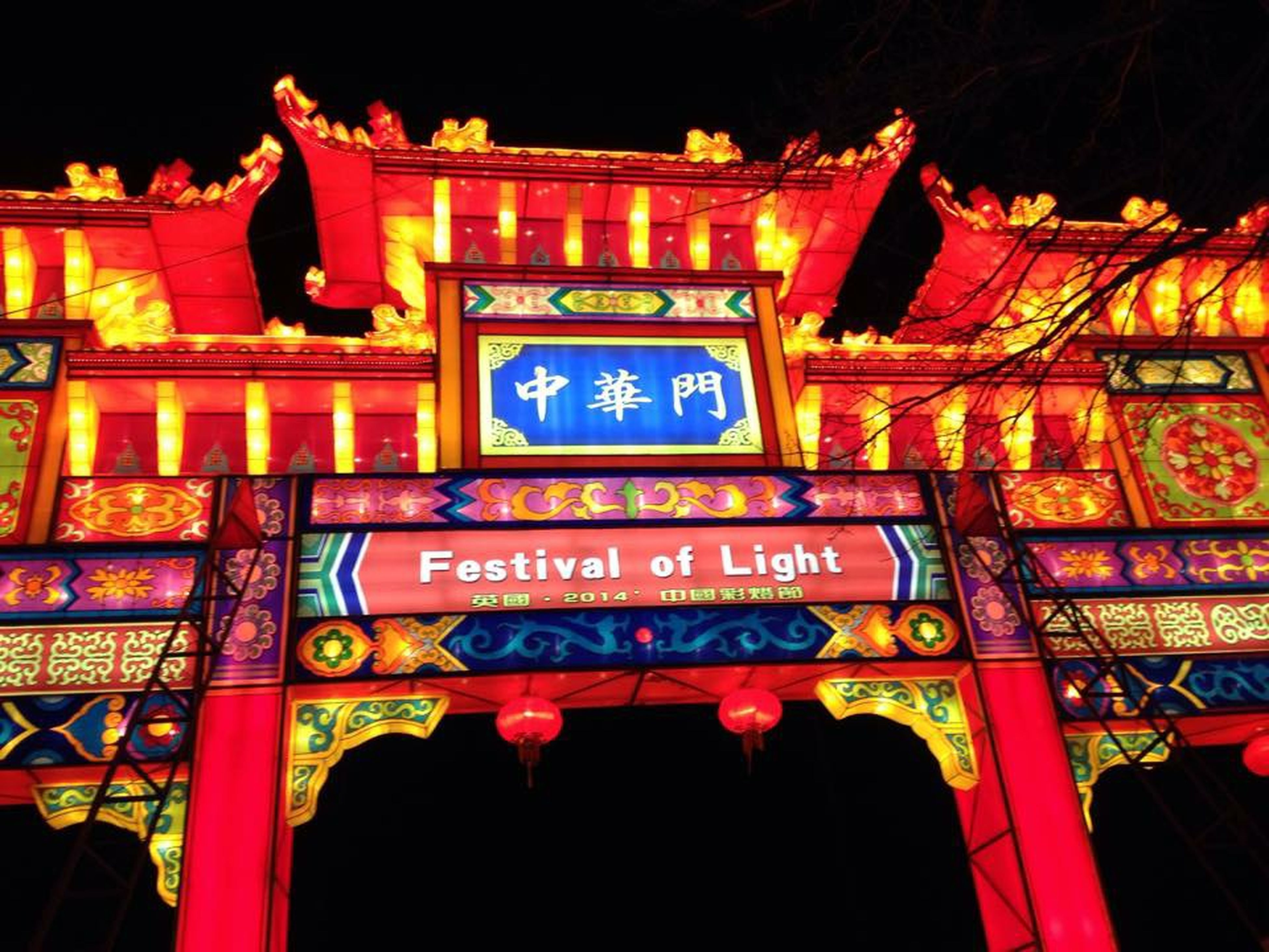 illuminated, night, text, low angle view, non-western script, built structure, western script, architecture, communication, religion, building exterior, lantern, spirituality, cultures, lighting equipment, multi colored, place of worship, red, culture, temple - building
