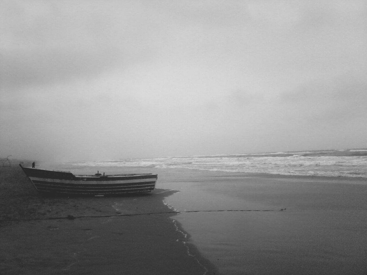 Lone Boat On Calm Beach Against The Sky