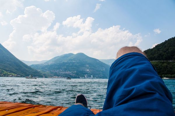 FloatingPiers Floating Piers Italy Sky Rear View One Person Sitting Relaxation Real People Men Nature Cloud - Sky Lifestyles Shoe Low Section Water Leisure Activity Outdoors Vacations Day Scenics Human Leg