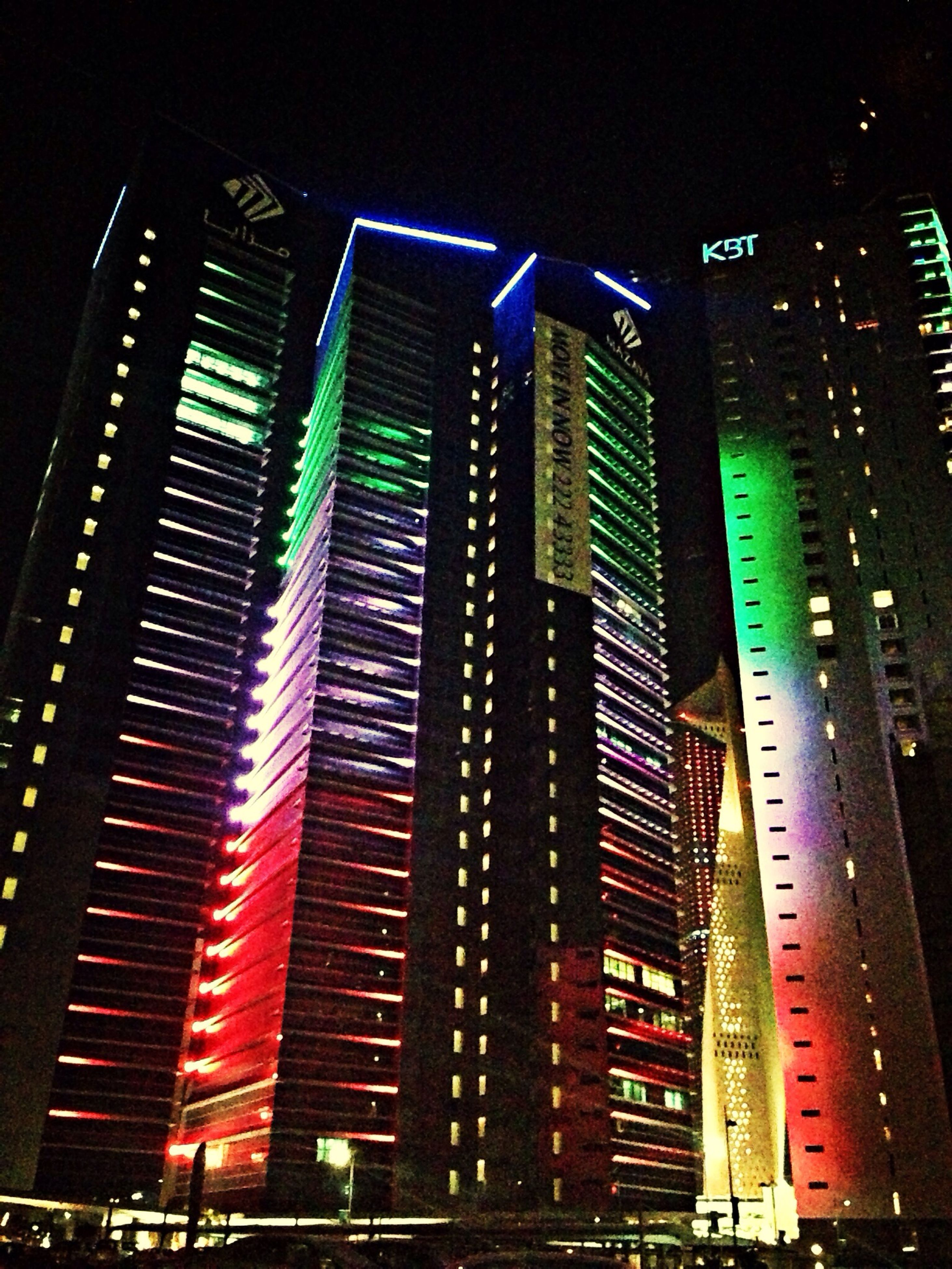 building exterior, architecture, illuminated, built structure, night, city, skyscraper, low angle view, tall - high, modern, tower, office building, building, city life, tall, sky, residential building, no people, outdoors, financial district