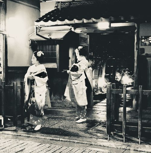 Geishas waiting for guests outside their tea house in Gyon Japan Historic Cultural Tourism Tradition Entertainment Blackandwhite Teahouse Geisha Gyon Kyoto Full Length Real People Store Men Rear View Retail  Two People Women