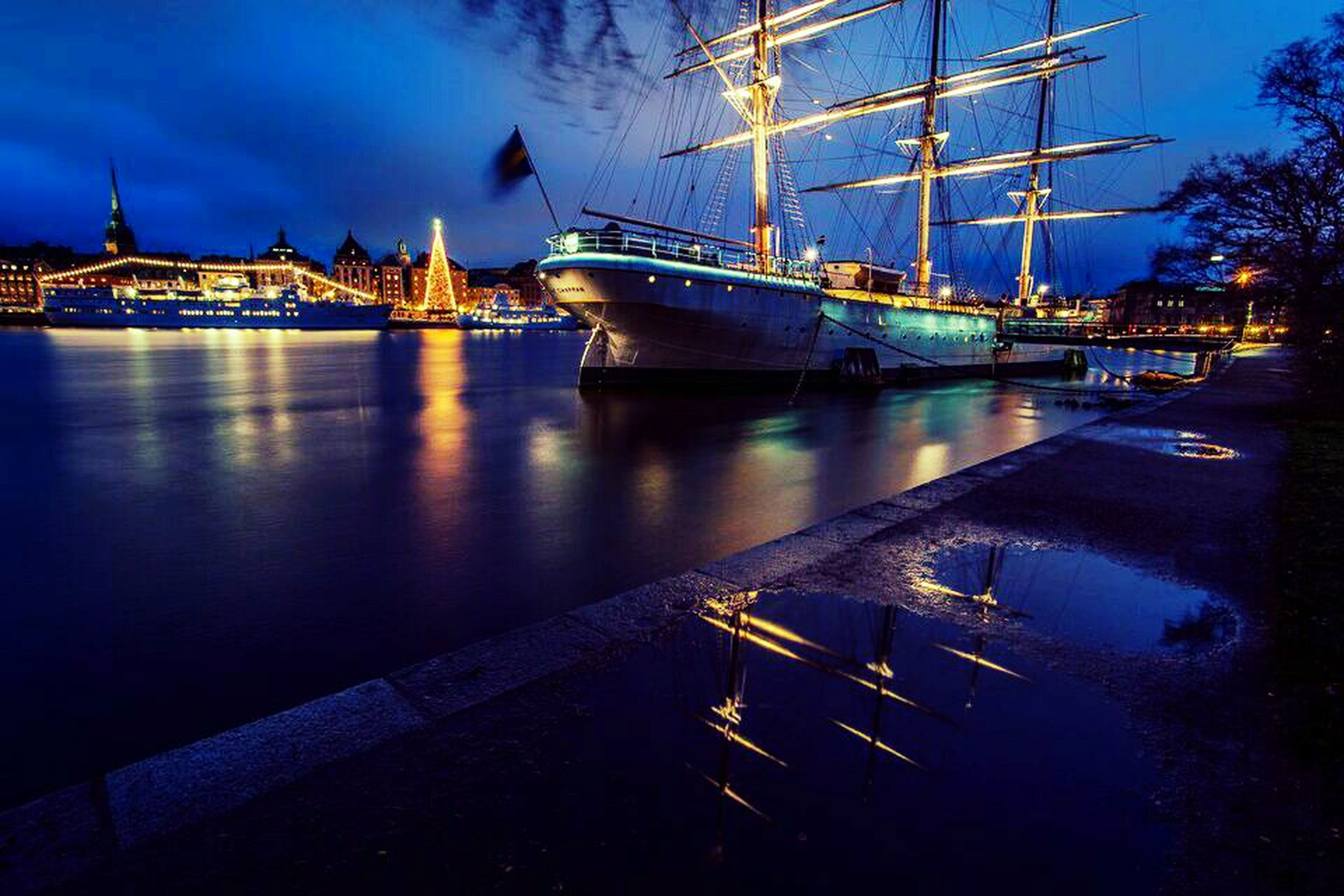 transportation, water, nautical vessel, sky, river, built structure, moored, bridge - man made structure, connection, mode of transport, blue, boat, illuminated, architecture, harbor, reflection, dusk, night, engineering, waterfront