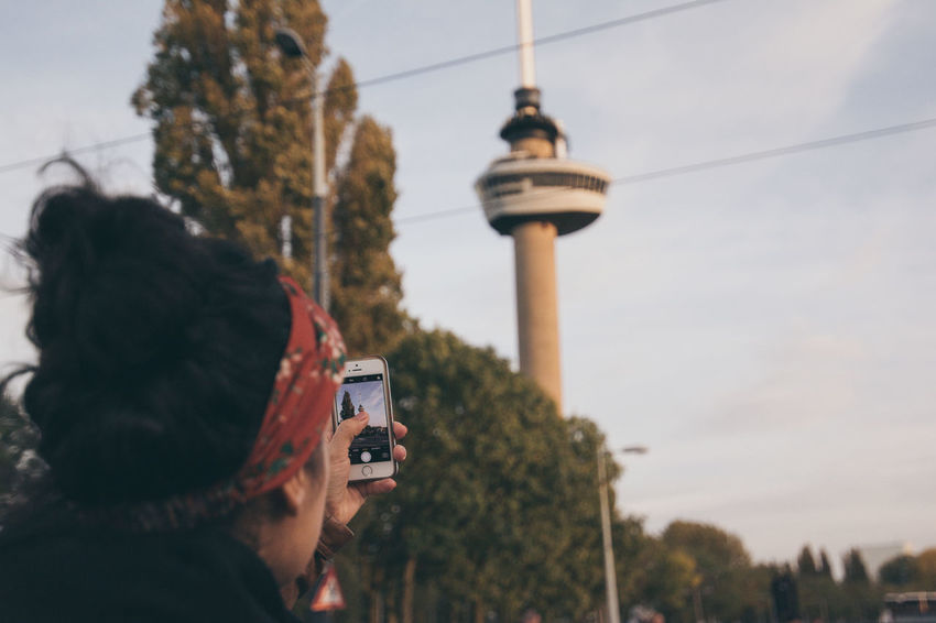 Woman Rotterdam Architecture Built Structure Communication Euromast Girl Holding Leisure Activity One Person Outdoors People Phone In Hand Photographing Photography Themes Real People Rear View Sky Smartphone Technology Tourism Tower Wireless Technology Women