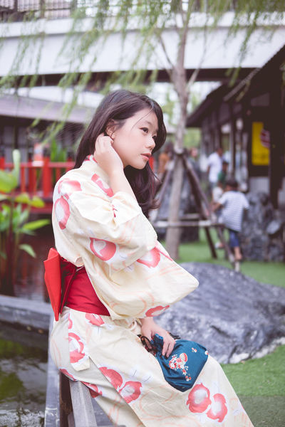 Architecture Beautiful Woman Black Hair Building Exterior Built Structure Casual Clothing Day Focus On Foreground Kimono Leisure Activity Lifestyles Nature One Person Outdoors Park - Man Made Space People Real People Side View Three Quarter Length Tree Young Adult Young Women