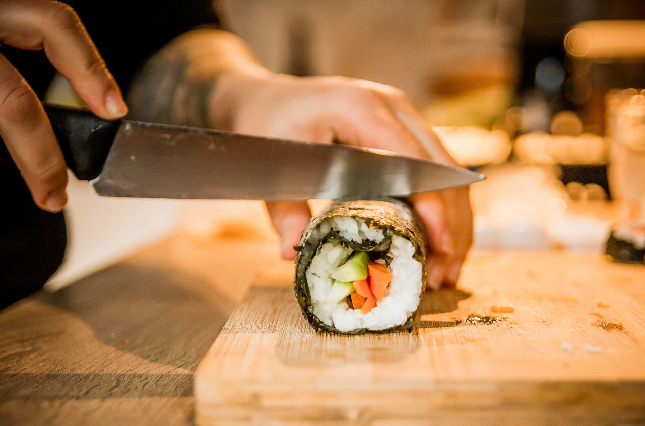 Cropped Image Of Man Cutting Sushi On Board