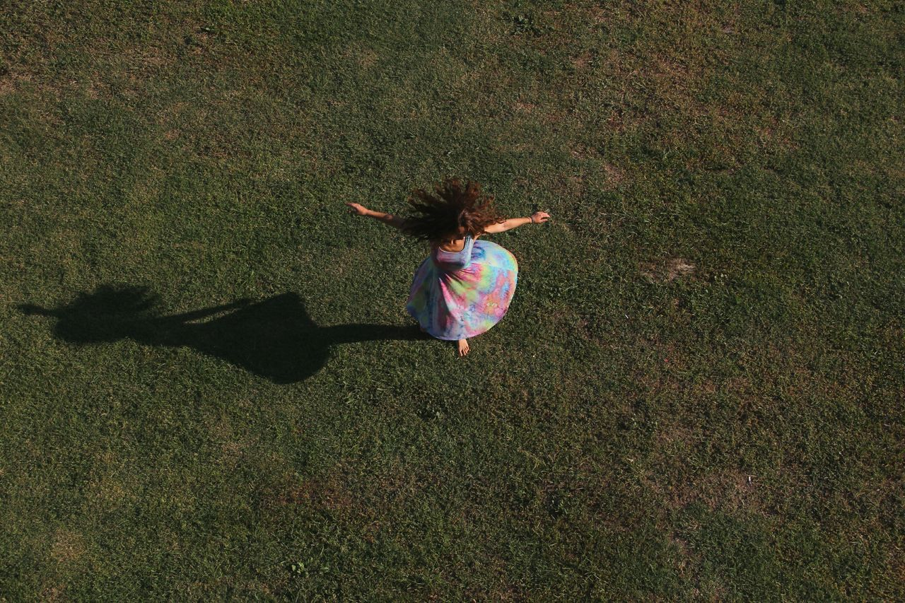grass, high angle view, girls, childhood, full length, field, one person, real people, shadow, leisure activity, day, outdoors, child, motion, growth, one girl only, nature, people