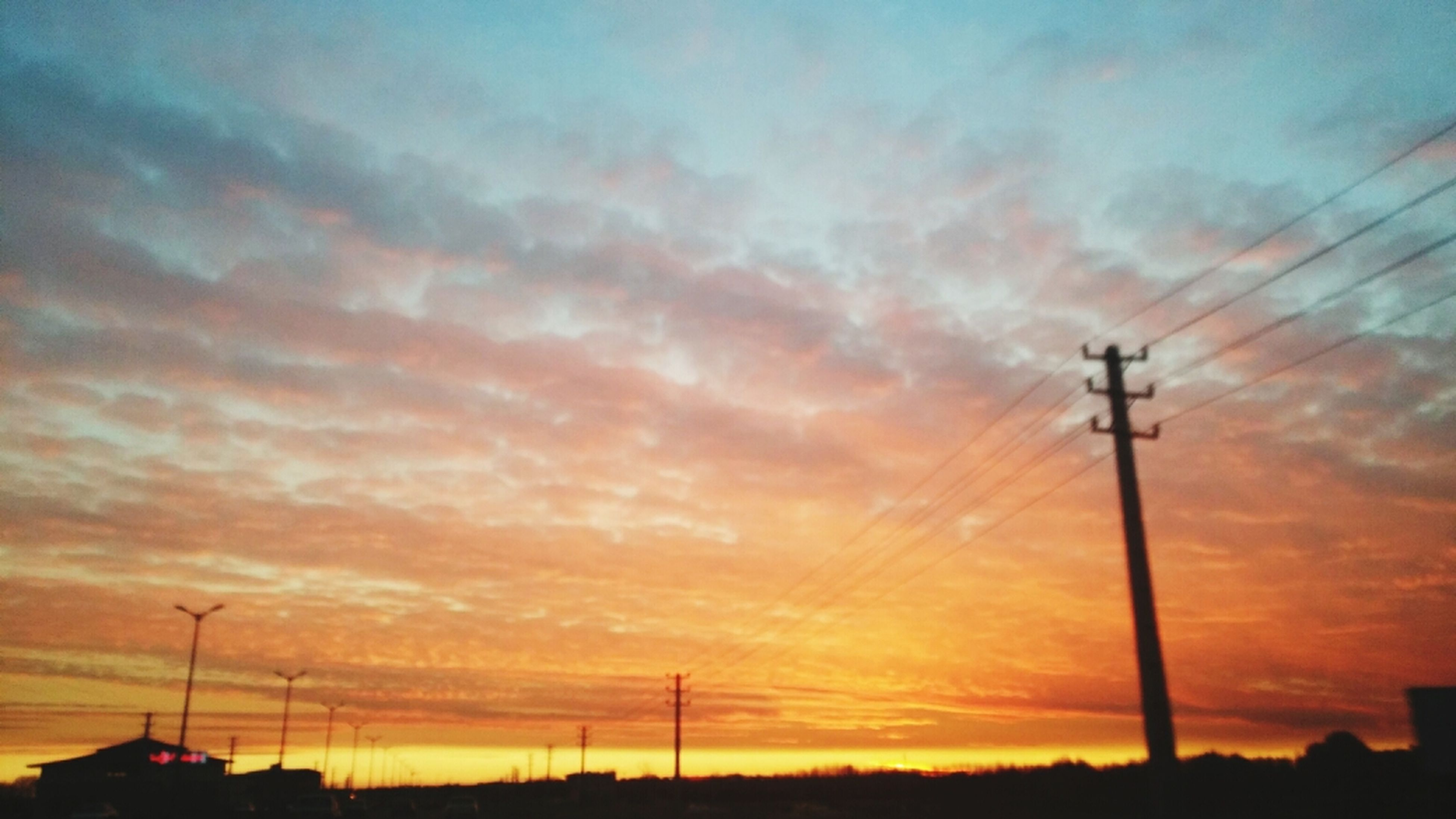 sunset, silhouette, orange color, sky, street light, low angle view, beauty in nature, cloud - sky, scenics, dramatic sky, technology, electricity pylon, tranquility, fuel and power generation, nature, power line, tranquil scene, lighting equipment, idyllic, electricity